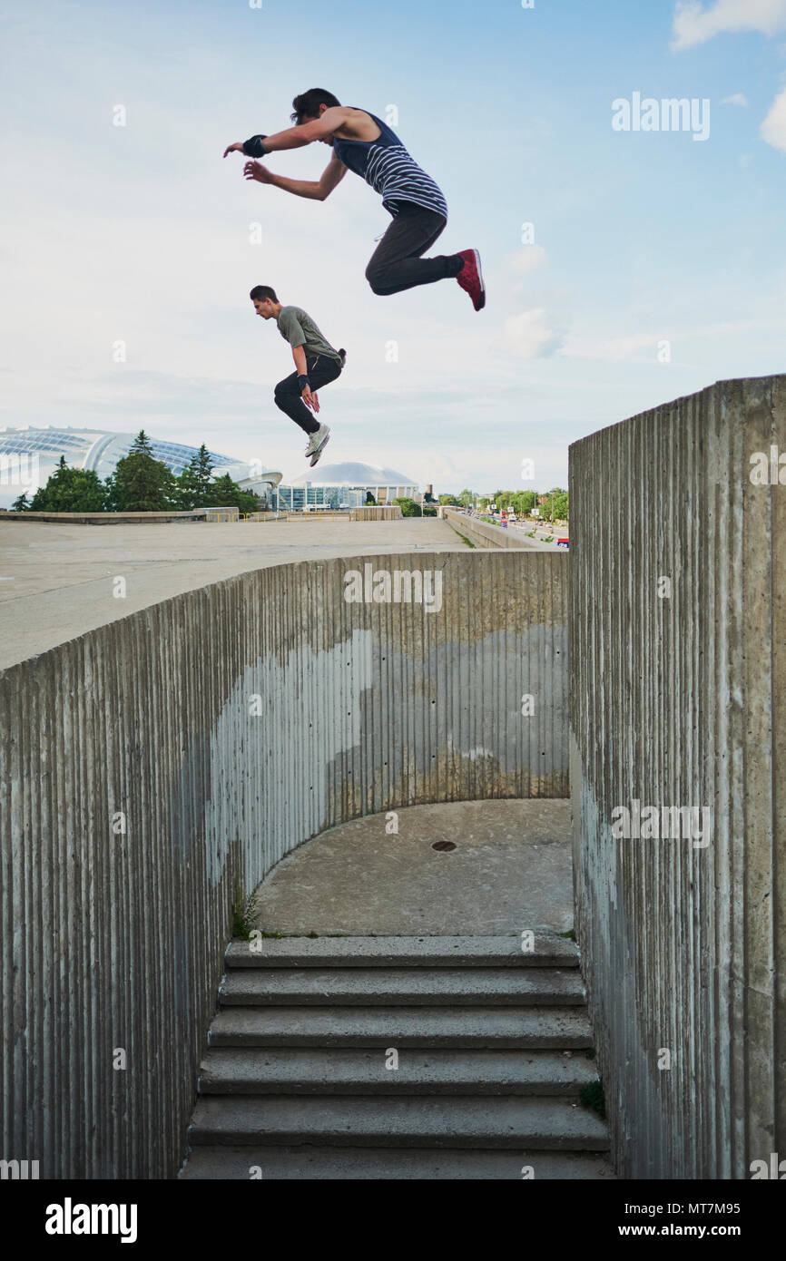Teenage free runners jumping off concrete structure and doing parkour - Stock Image