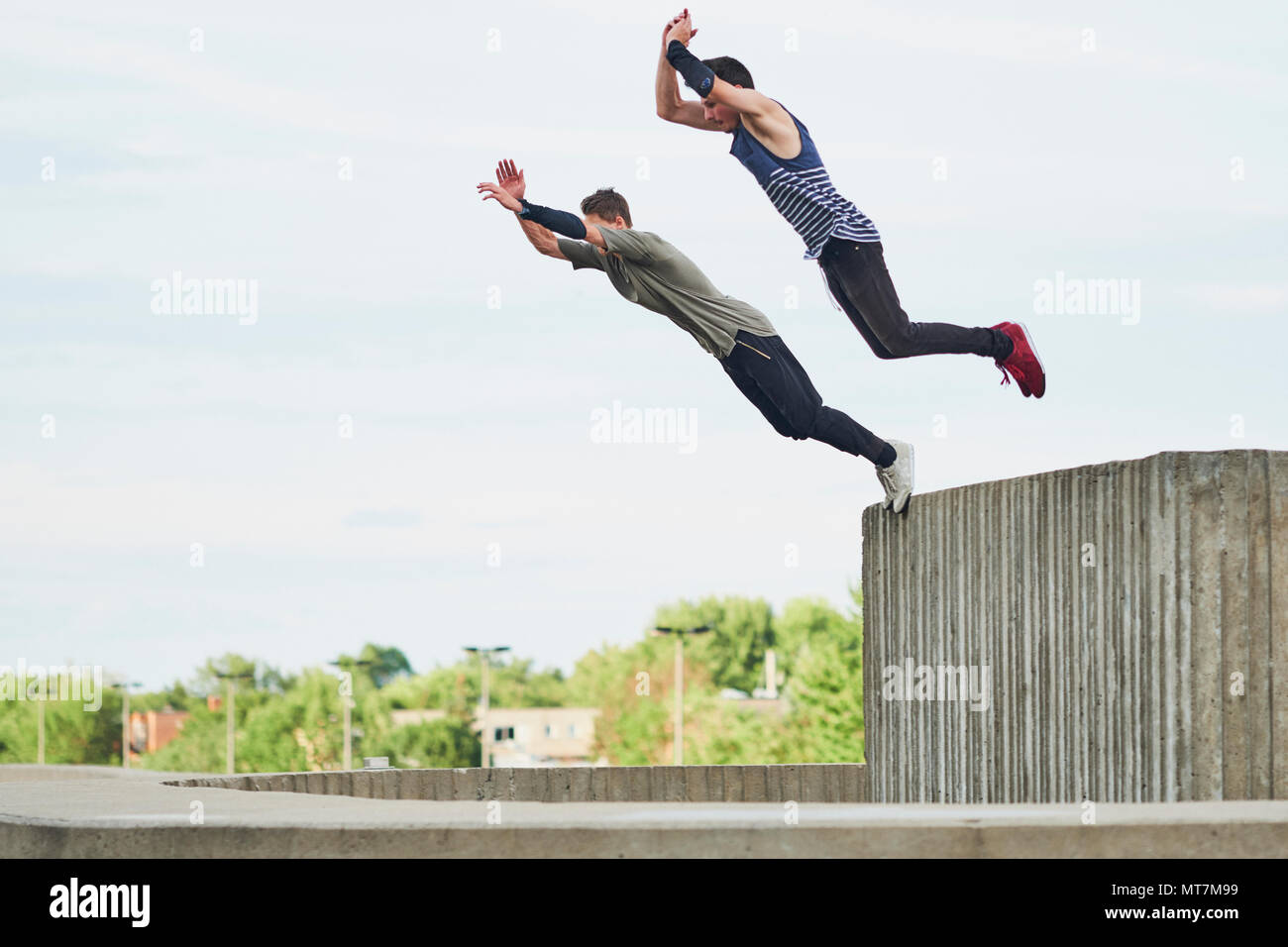Teenage free runners jumping off concrete structure and doing parkour Stock Photo