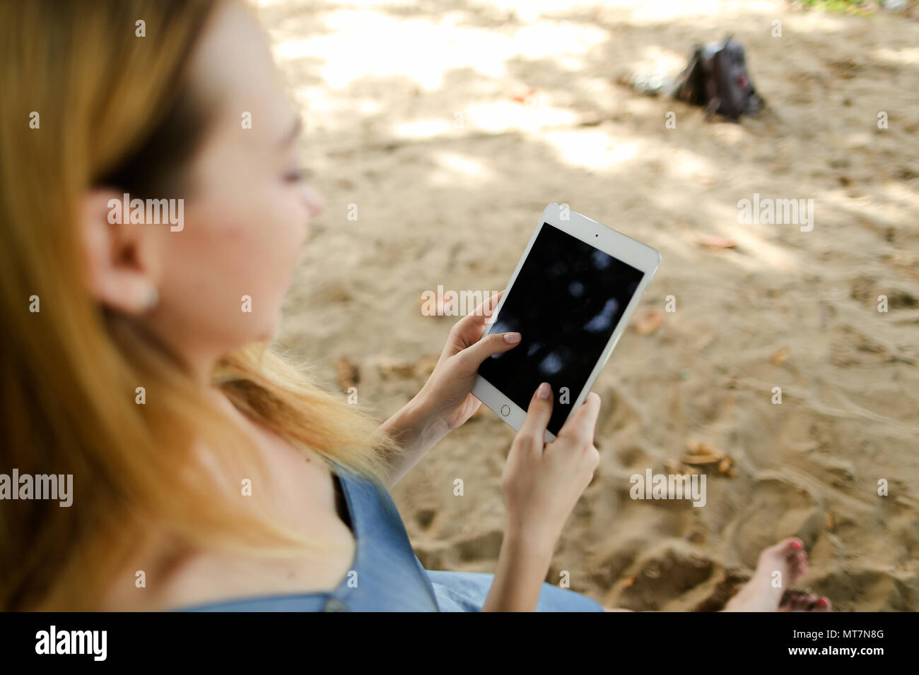 Young woman using tablet in sand background. - Stock Image