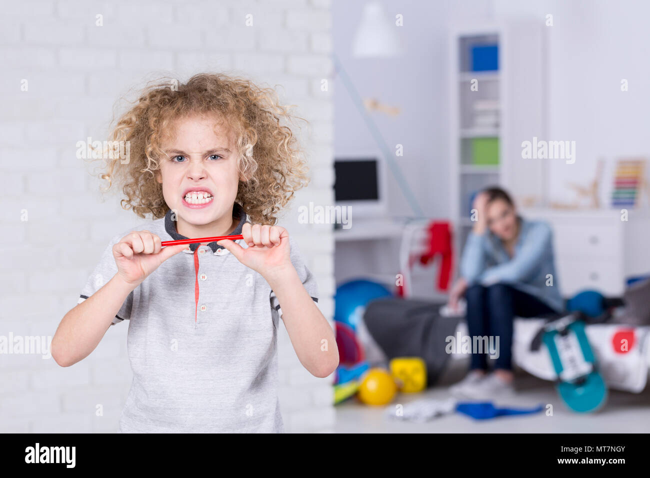 Angry child baring his teeth, trying to break pencil Stock Photo