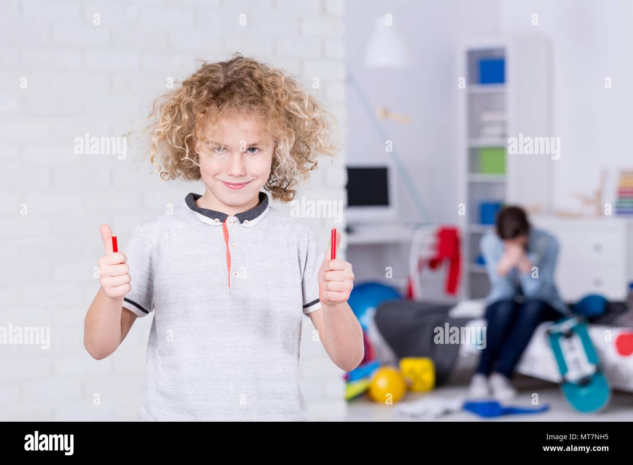 Mean school boy holding pieces of broken pencil - Stock Image