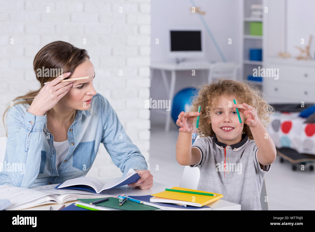 Impatient mother doing homework with distracted son - Stock Image
