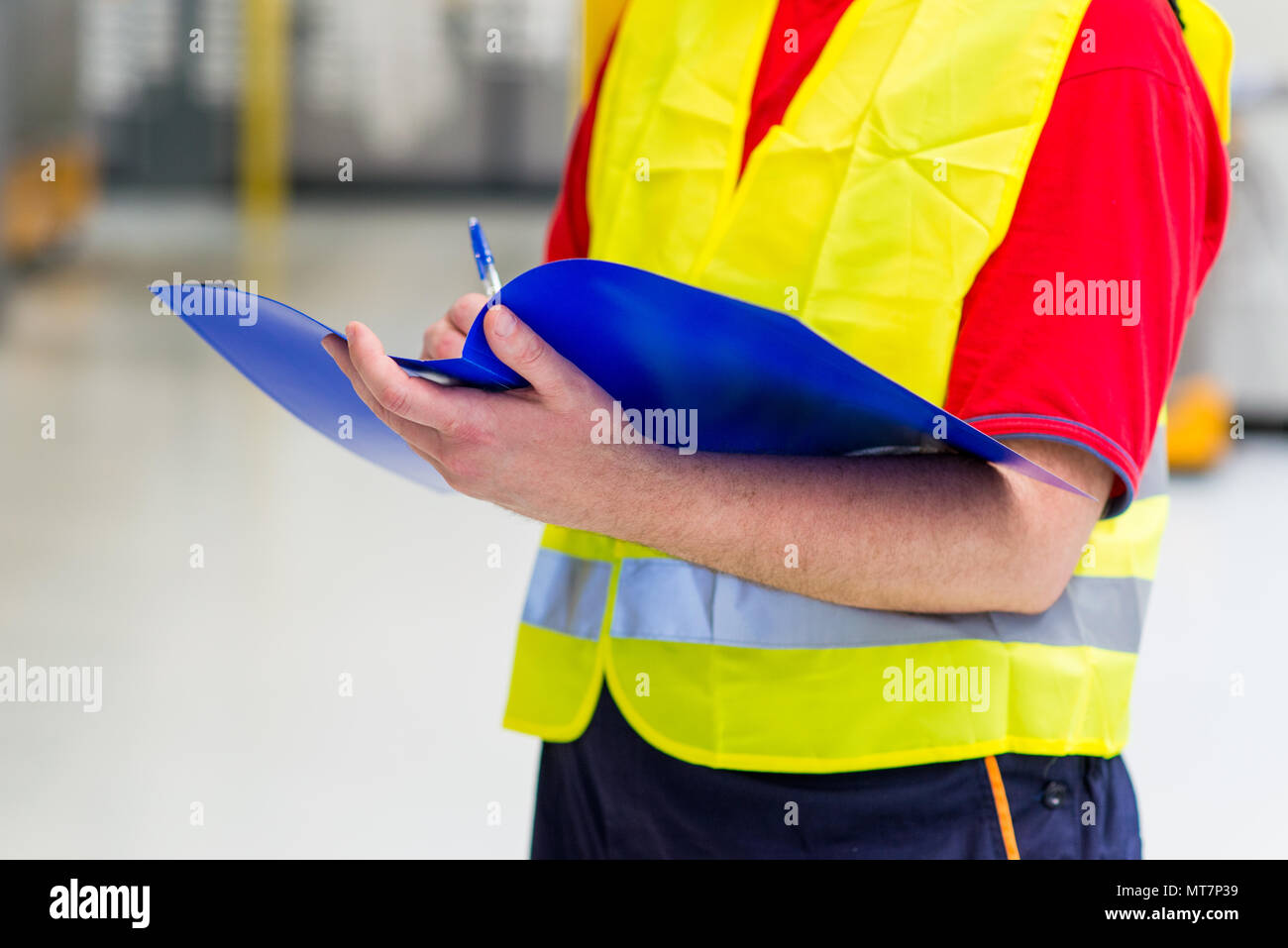 Factory supervisor in yellow reflective west. Factory engineer holding blue folder with documents - Stock Image