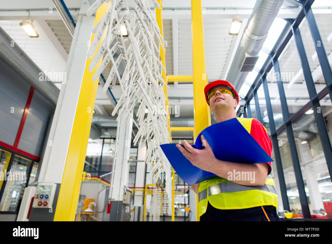 Factory supervisor in yellow reflective west with red helmet. Factory engineer checking production line holding blue folder with documents - Stock Image