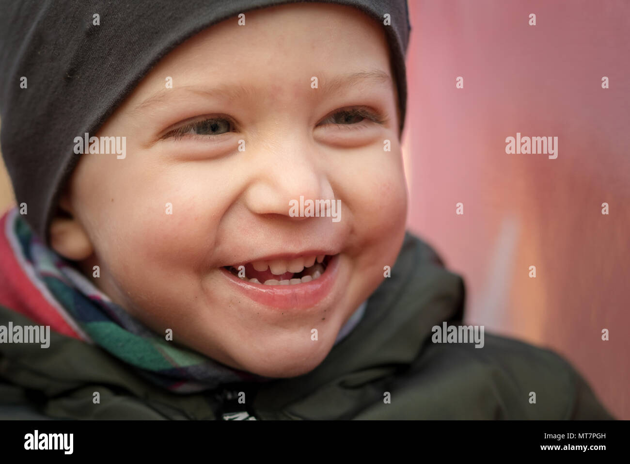 Happy baby boy with a cap laughing loudly sitting on a children slide,close up. - Stock Image