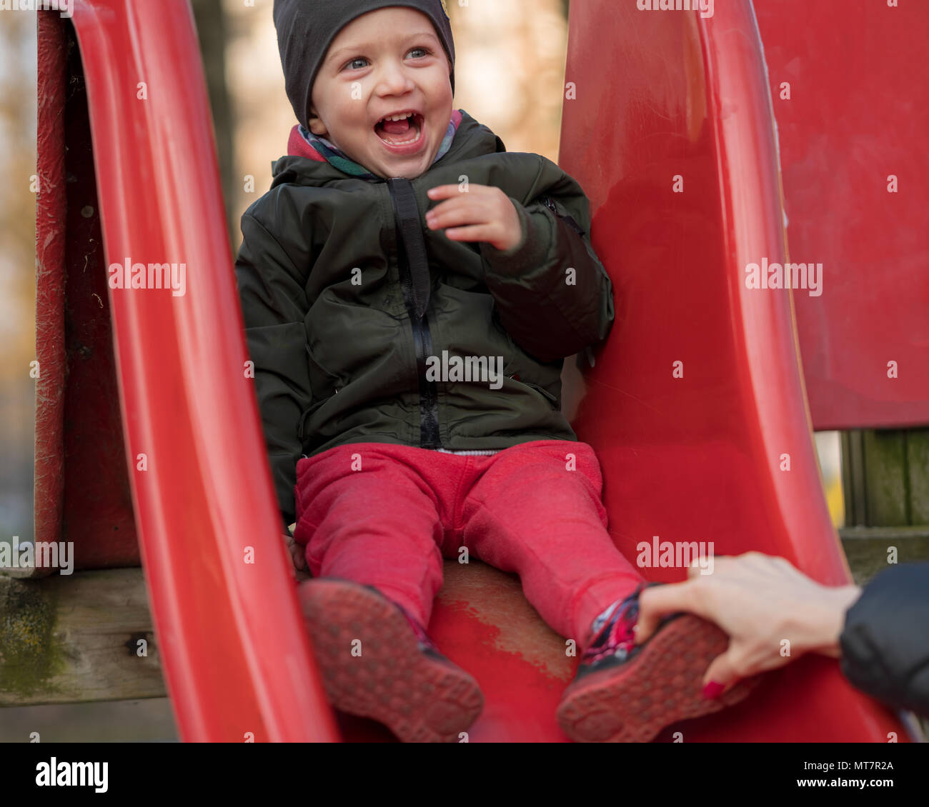Happy kid boy with a cap laughing loudly sitting on a children slide at kid's playground. Active childhood concept - Stock Image
