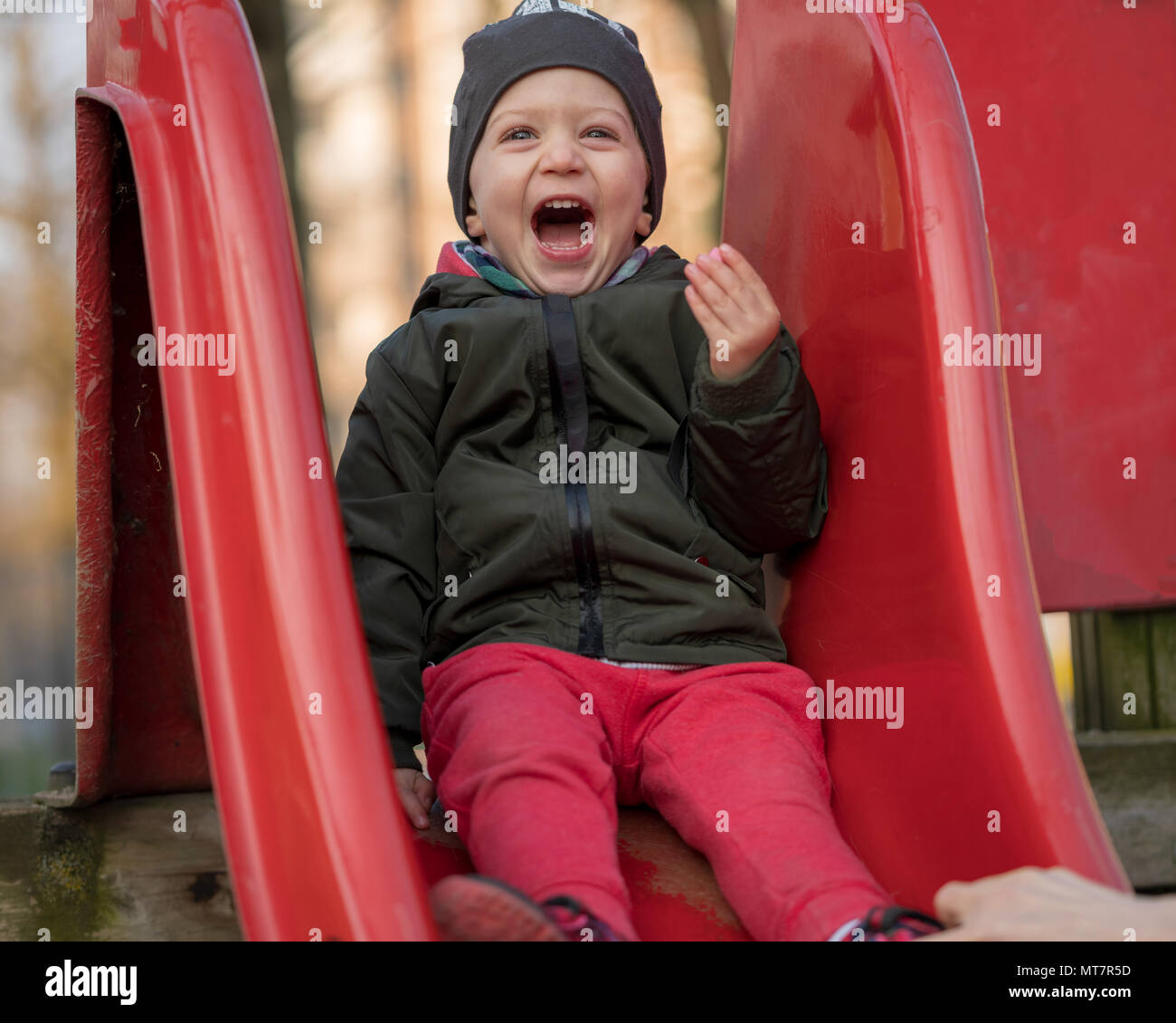 Happy baby boy with a cap laughing loudly sitting on a children slide at kid's playground. Active childhood concept - Stock Image