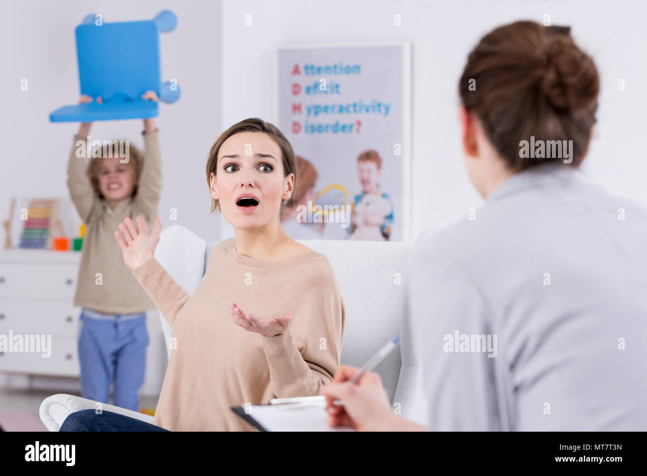 Violent child and terrified mother during session with psychologist - Stock Image