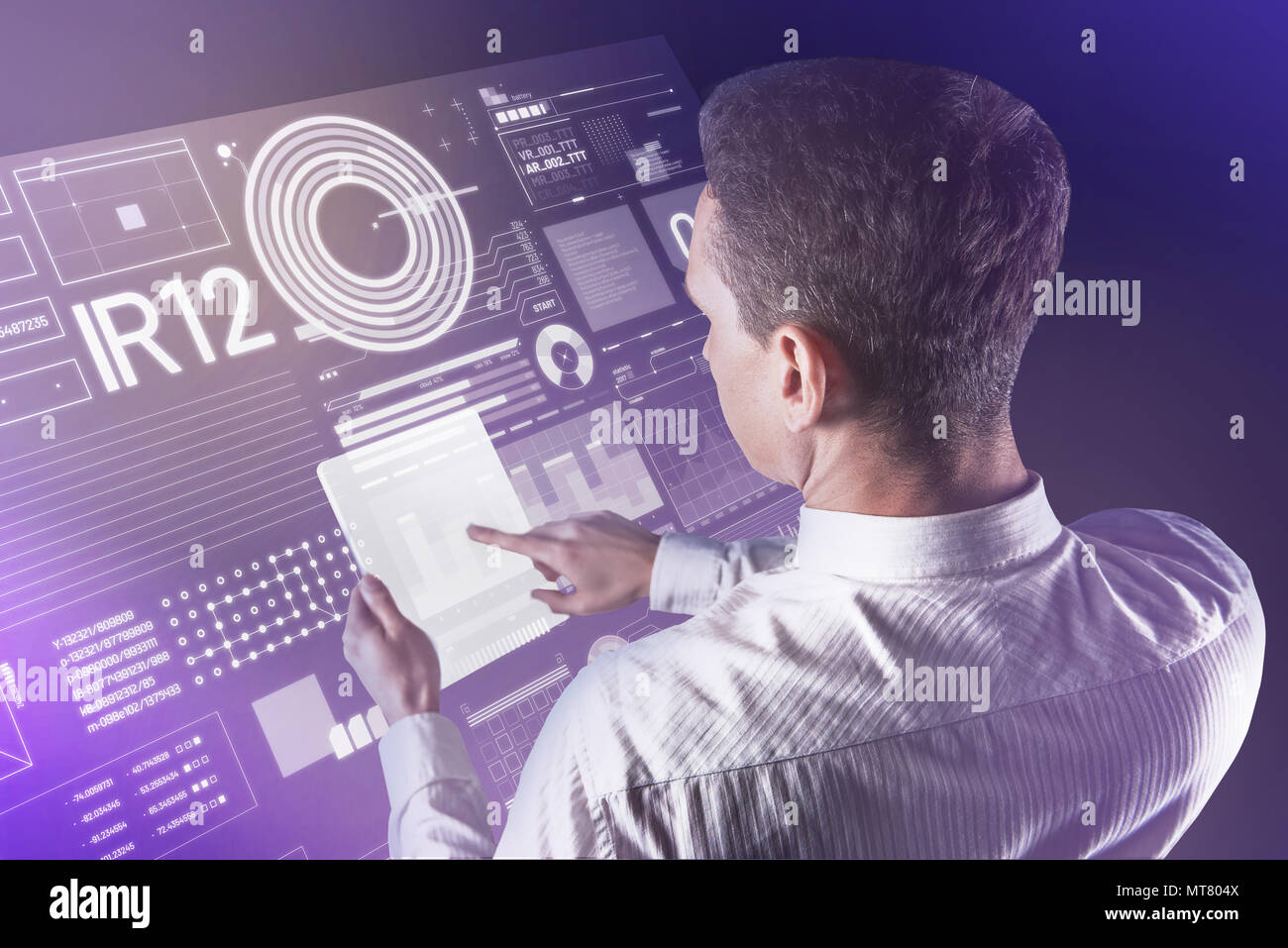 Calm young man holding a futuristic tablet and checking the information - Stock Image