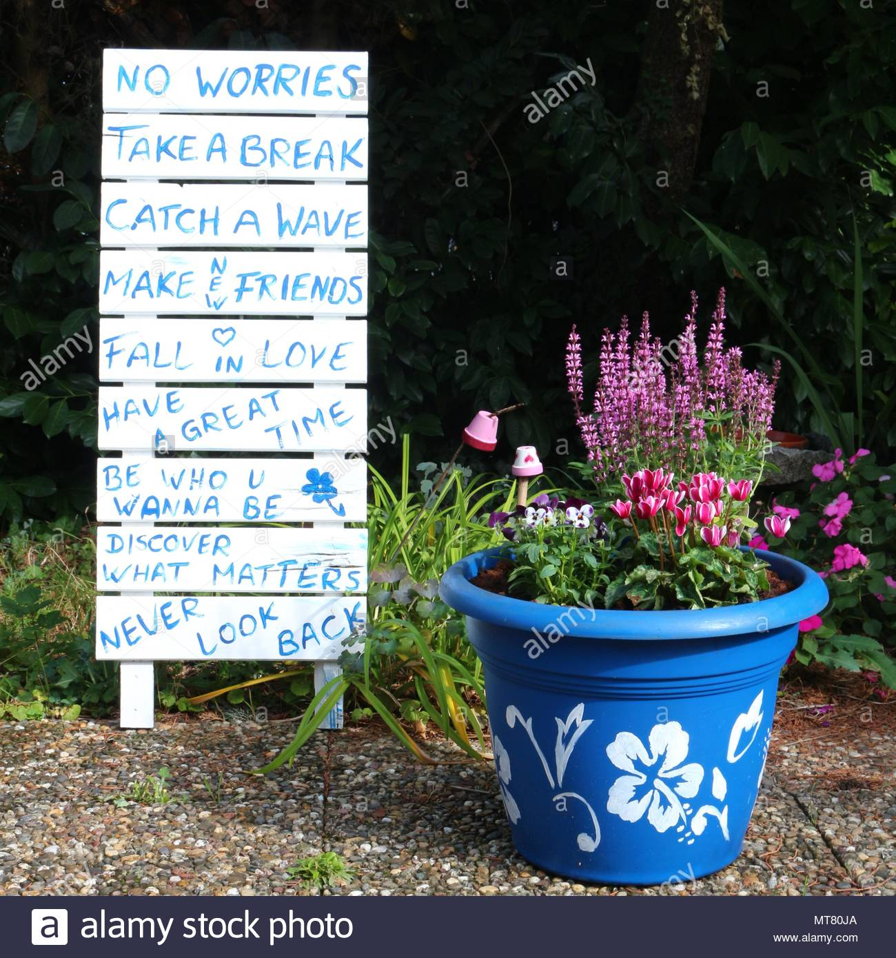 Garden decoration with painted pot and wise sayings written on a board - Stock Image