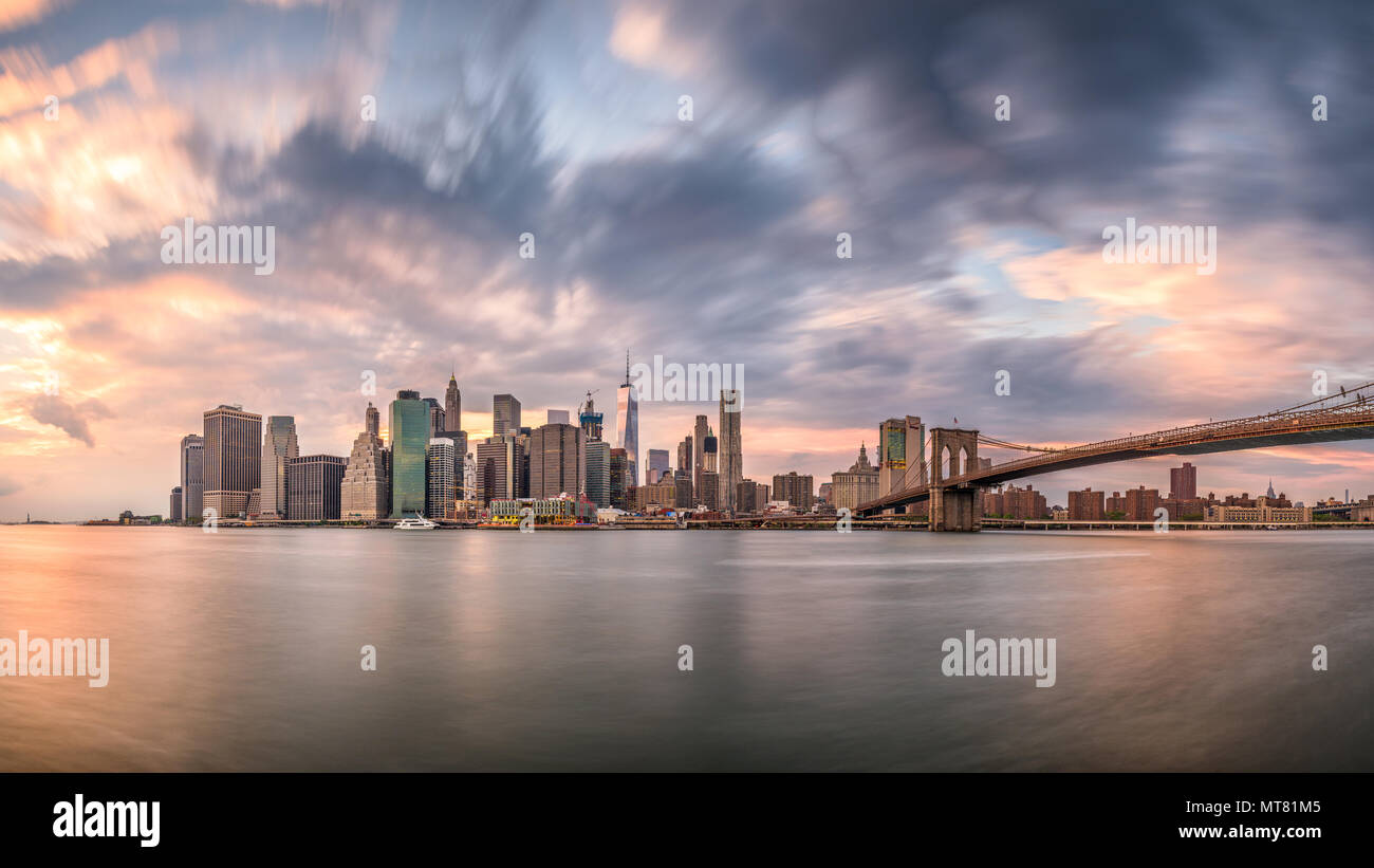 New York, New York, USA skyline of Manhattan on the East River with Brooklyn Bridge a dusk. - Stock Image