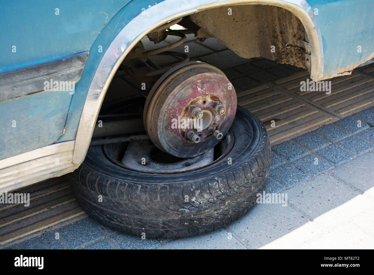 Old car waiting for the wheel. Car without tire need to be repaired. - Stock Image