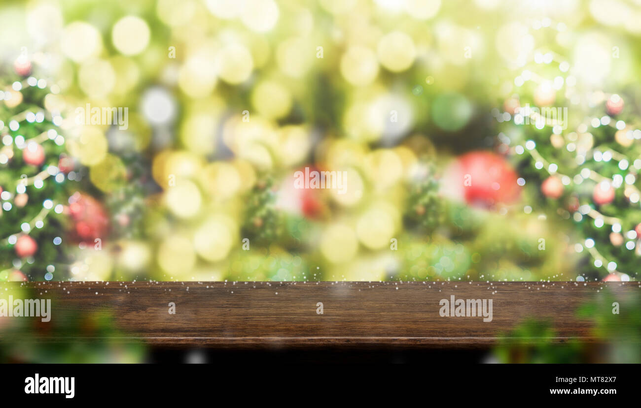 Empty dark brown wood table top with abstract blur christmas tree red decor ball and snow fall background with bokeh light,winter Holiday backdrop,Moc - Stock Image