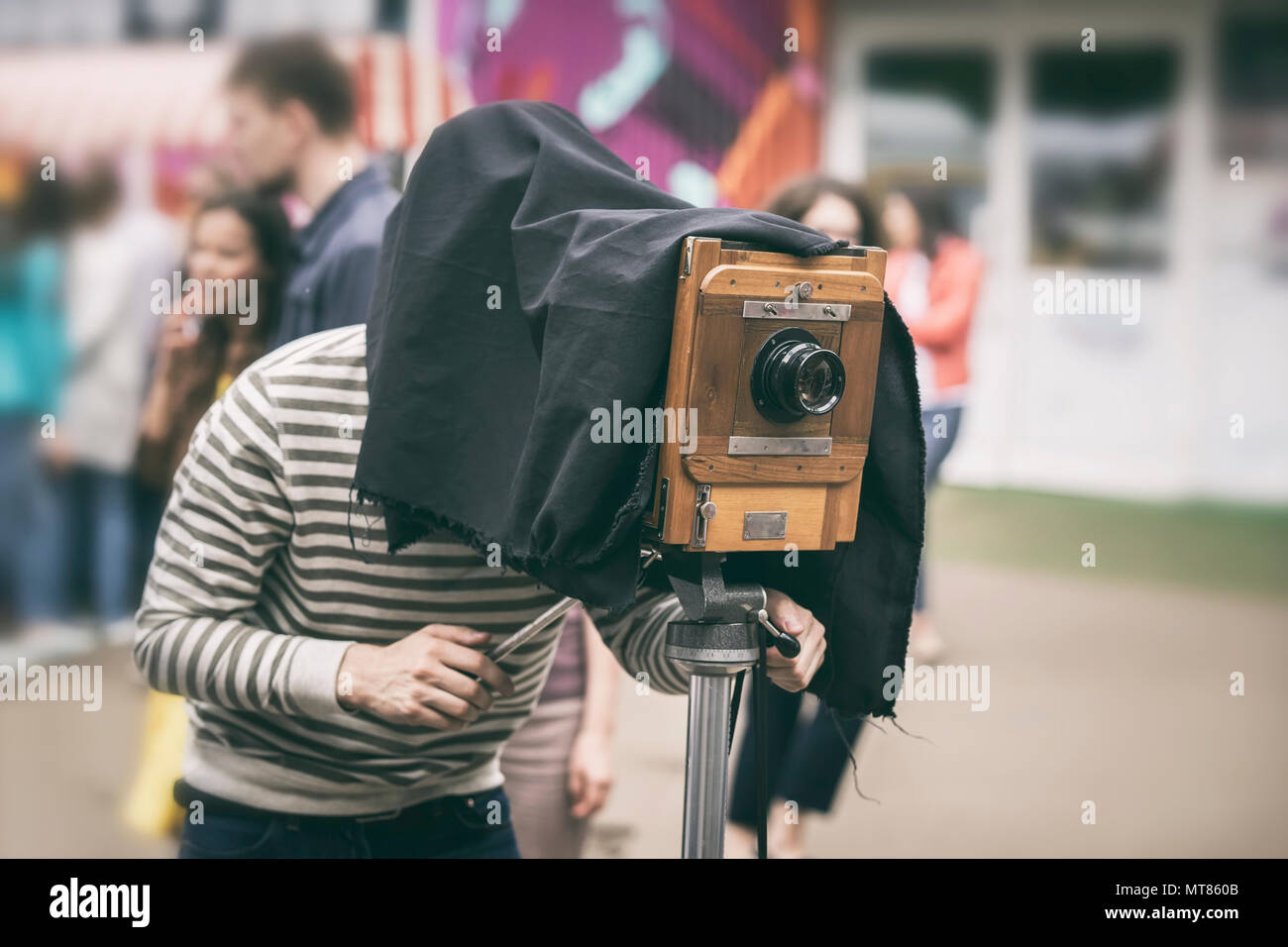 Photographer with antiquity vintage wooden camera under dark cloth cape photographing passers - old classical action, rarity concept - Stock Image