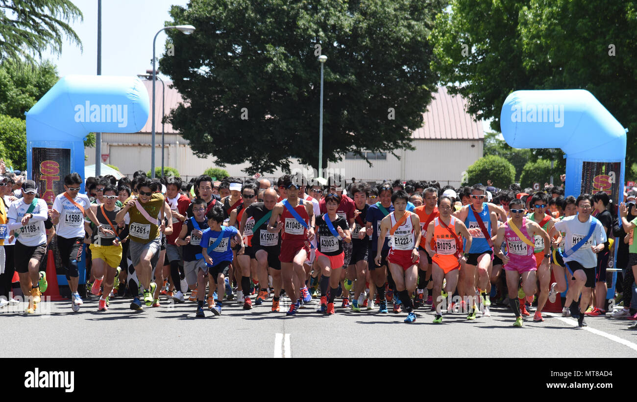 Competitors start running the main event, the Ekiden at Yokota Air Base, Japan, June 4, 2017. An Ekiden is a Japanese long distance relay that consists of teams of runners covering a certain distance. The Yokota Ekiden is 20K in distance made up of four runners each running a 5K. (U.S. Air Force photo by Machiko Arita) - Stock Image