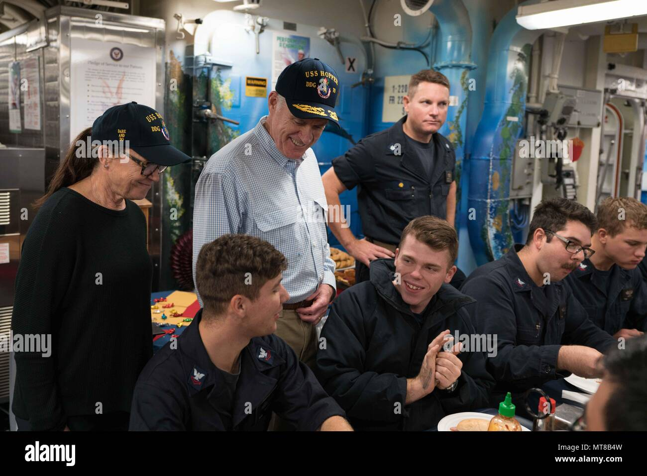 ARABIAN GULF (Nov. 23, 2017) Secretary of the Navy (SECNAV) Richard V. Spencer (center), and his wife, Sarah Pauline Spencer, meet with crewmembers of the Arleigh Burke-class guided-missile destroyer USS Hopper (DDG 70) on the ship's mess decks during the SECNAV's visit to the ship on Thanksgiving Day. Hopper is deployed to the U.S. 5th Fleet area of operations in support of maritime security operations to reassure allies and partners and preserve the freedom of navigation and the free flow of commerce in the region. (U.S. Navy photo by Fire Controlman 2nd Class Jonathan Clegg/Released) - Stock Image