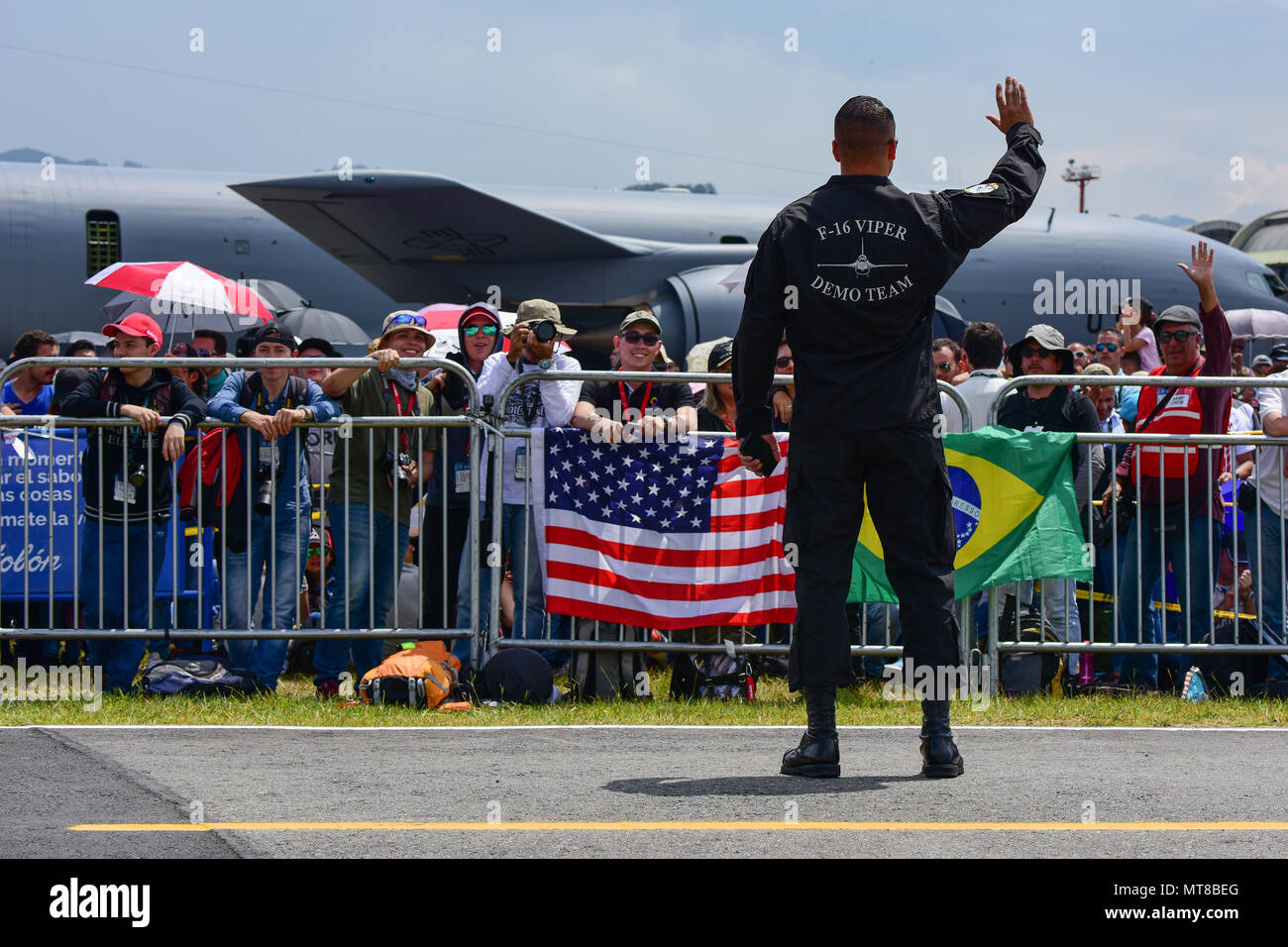 U.S. Air Force Tech. Sgt. Stephen Mullins, an avionics technician assigned to the Air Combat Command's Viper East Demo Team, waves to the crowd at José María Córdova International Airport during Feria Aeronautica Internacional—Colombia 2017 in Rionegro, Colombia, July 15, 2017. The United States Air Force is participating in the four-day air show with two South Carolina Air National Guard F-16s as static displays, plus static displays of a KC-135, KC-10, along with an F-16 aerial demonstration by the Air Combat Command's Viper East Demo Team. United States military participation in the air sho - Stock Image