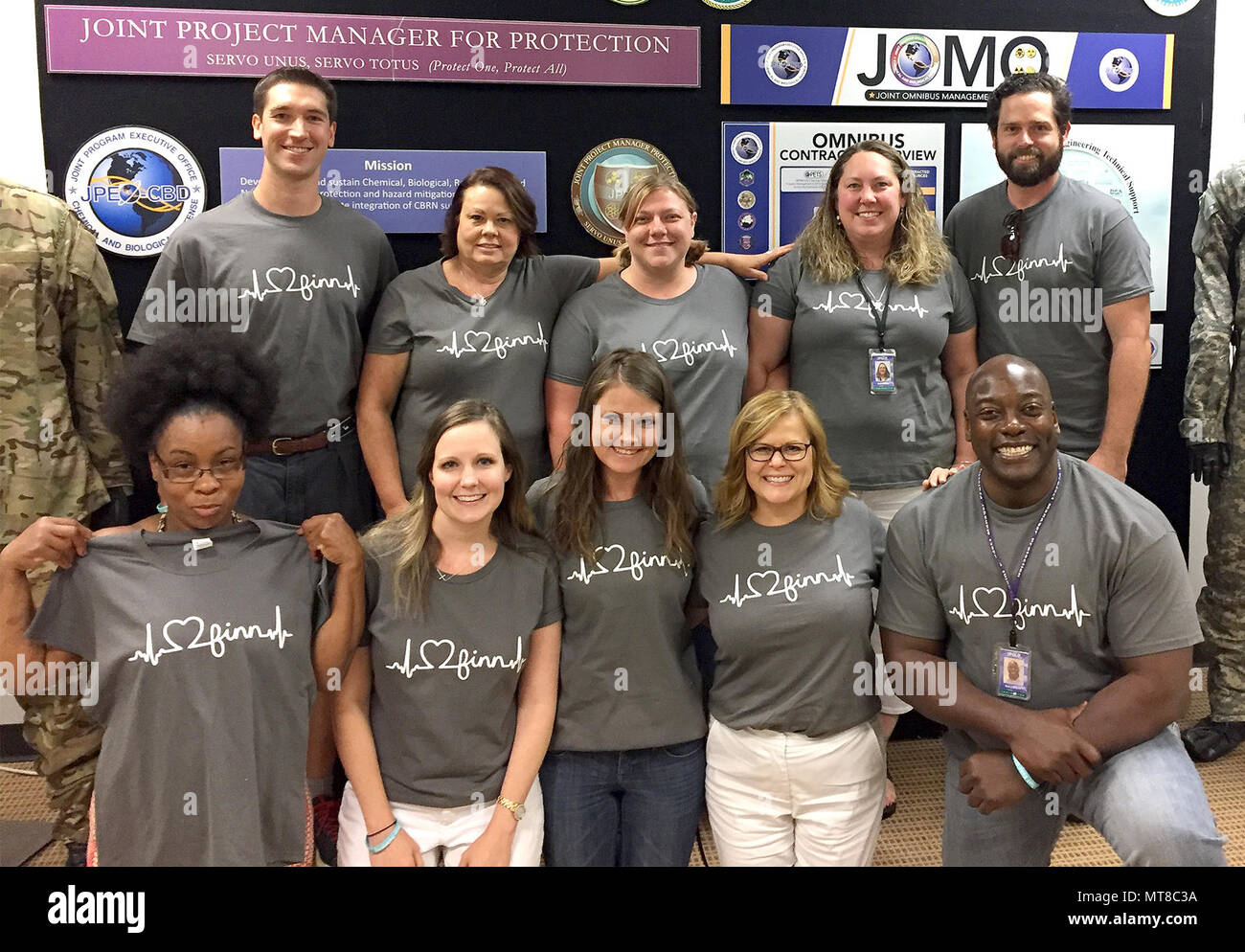 "The Joint Project Manager for Protection Team at Marine Corps Systems Command surprise Financial Management Analyst Michael Blumenthal with ""I love Finn"" shirts. Michael felt supported by his colleagues when his youngest son Finn had his second open heart surgery last September. - Stock Image"