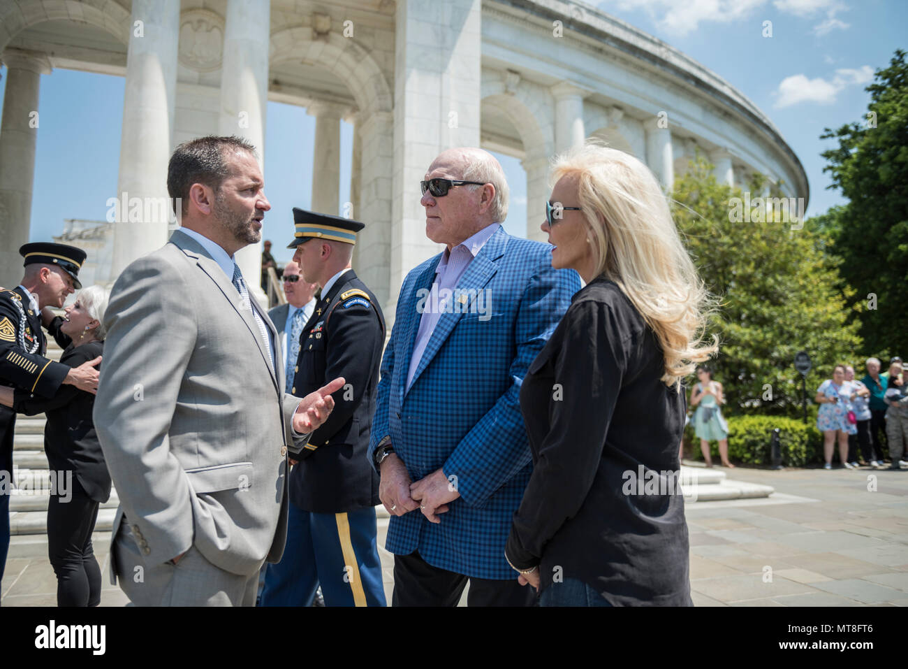Micheal Migliara (left), director of events and ceremonies, Arlington National Cemetery; Terry Bradshaw (center), representative of United Service Organization (USO) Metro; and his wife, Tammy Bradshaw (right); speak at the west steps of the Memorial Amphitheater at Arlington National Cemetery, Arlington, Virginia, May 11, 2018. Bradshaw participated in an Army Special Honors Wreath-Laying at the Tomb of the Unknown Soldier during his visit. (U.S. Army photo by Elizabeth Fraser / Arlington National Cemetery/ released) - Stock Image