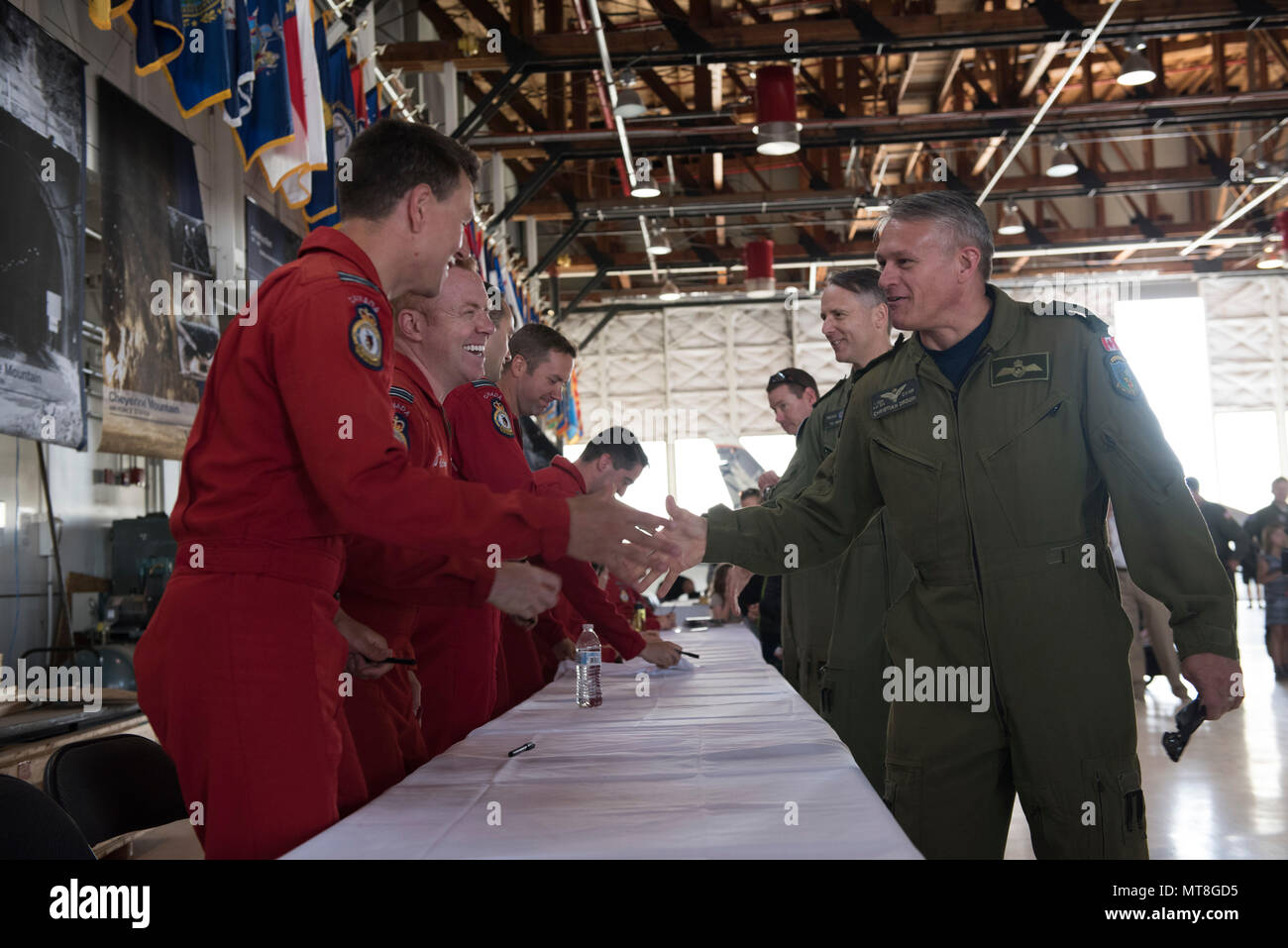 Members of the Royal Canadian Air Force's Snowbirds aerial demonstration team greet guests at the North American Aerospace Defense Command's 60th Anniversary Ceremony on Peterson Air Force Base Colorado, May 12, 2018. The ceremony and static display of various NORAD aircraft was the culmination of a three-day event, which included a media tour of Cheyenne Mountain Air Force Station, the dedication of a cairn outside the commands' headquarters building memorializing the Canadians who have passed away while serving NORAD, and a fly over in missing-man formation performed by the Royal Canadian Ai Stock Photo