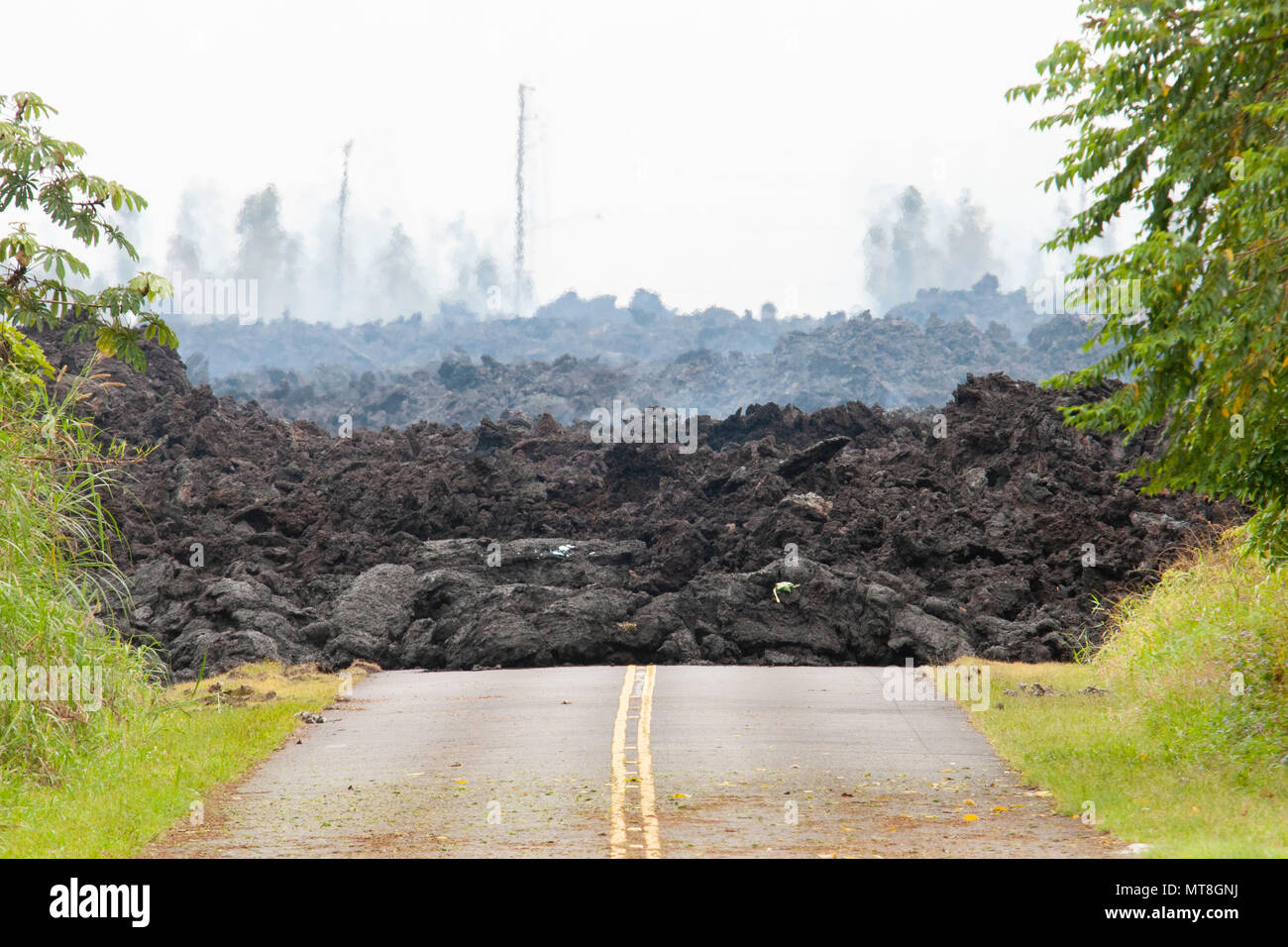 A lava roadblock covers a residential road May 12, 2018, at Leilani Estates, Pahoa, Hawaii. Members of the Hawaii Army and Air National Guard have been activated in order to assemble Task Force Hawaii, which is providing traffic assistance, presence patrols and supporting local government agencies with the volcano outbreak relief effort. (U.S. Air National Guard photo by Senior Airman John Linzmeier) - Stock Image