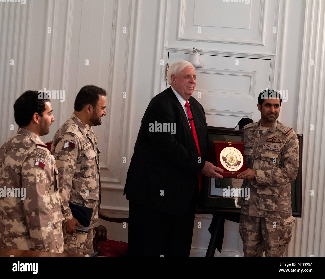 West Virginia Governor Jim Justice accepts a coin from the Qatari
