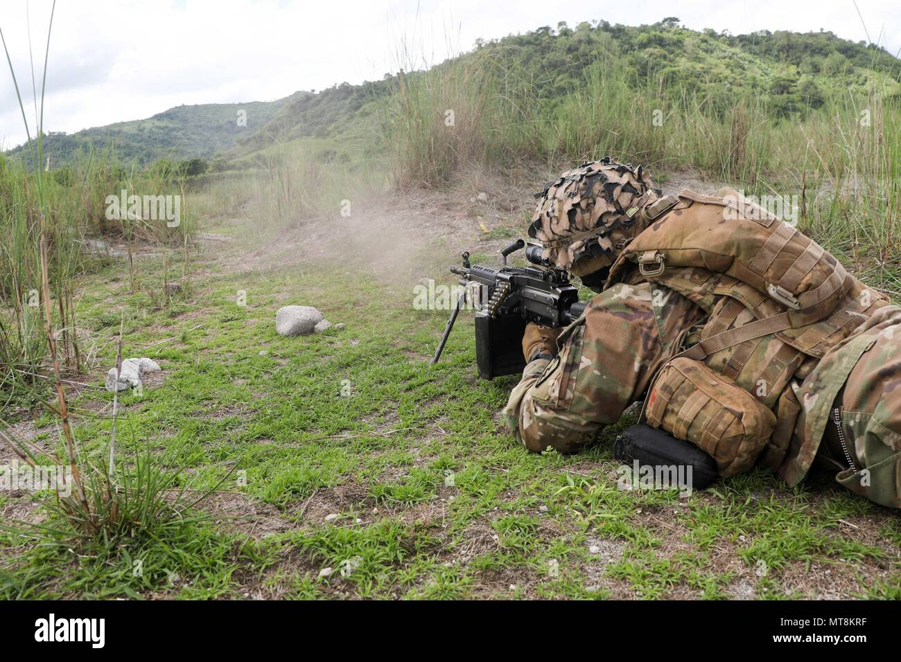 A U.S. Army Soldier provides cover fire as Soldiers from C Company, 1st Battalion, 21st Infantry Regiment, 2nd Infantry Brigade Combat Team, 25th Infantry Division maneuver to their objective during a combined arms live-fire exercise (CALFEX) at Colonel Ernesto Ravina Air Base, Tarlac, Philippines May 15, 2018, as part of Exercise Balikatan. The CALFEX is designed to demonstrate cooperation and interoperability between Philippine and U.S. forces as the two militaries continue their commitment to train and share information to improve their ability to coordinate a multilateral response to crisi - Stock Image