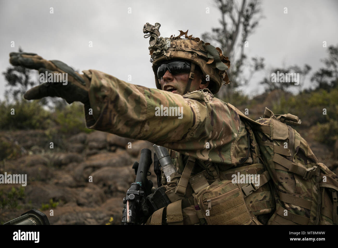 U.S. Army Trooper assigned to 2nd Squadron, 14th Calvary Regiment, 2nd Infantry Brigade Combat Team, 25th Infantry Division signals a movement direction during a Combined Arms Live Fire Exercise (CALFEX) at Pohakuloa Training Area, Hawaii, May 15, 2018. The CALFEX utilizes all the enablers available to the unit in order to increase interoperability, concentrate combat power and mass effects on the objective. (U.S. Army photo by 1st Lt. Ryan DeBooy) - Stock Image