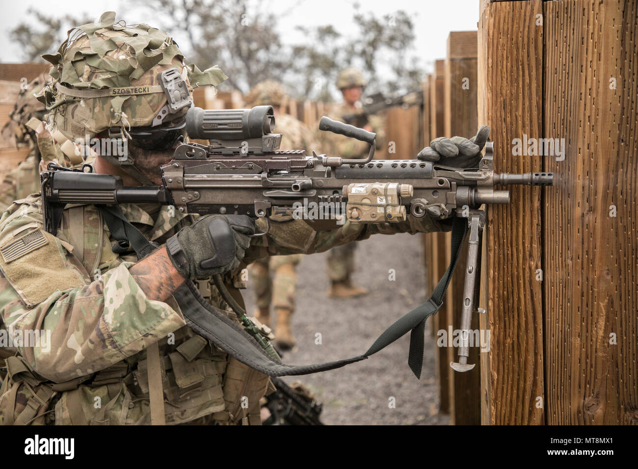 U.S. Army Trooper assigned to 2nd Squadron, 14th Calvary Regiment, 2nd Infantry Brigade Combat Team, 25th Infantry Division returns fire with an M249 Squad Automatic Weapon during a Combined Arms Live Fire Exercise (CALFEX) at Pohakuloa Training Area, Hawaii, May 15, 2018. The CALFEX utilizes all the enablers available to the unit in order to increase interoperability, concentrate combat power and mass effects on the objective. (U.S. Army photo by 1st Lt. Ryan DeBooy) - Stock Image