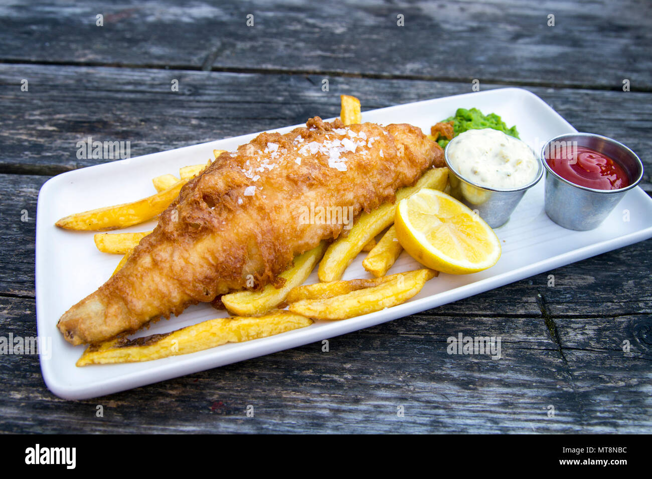 Plate of breaded fish and chips with mushy peas and tartar sauce served on a wooden table - Stock Image