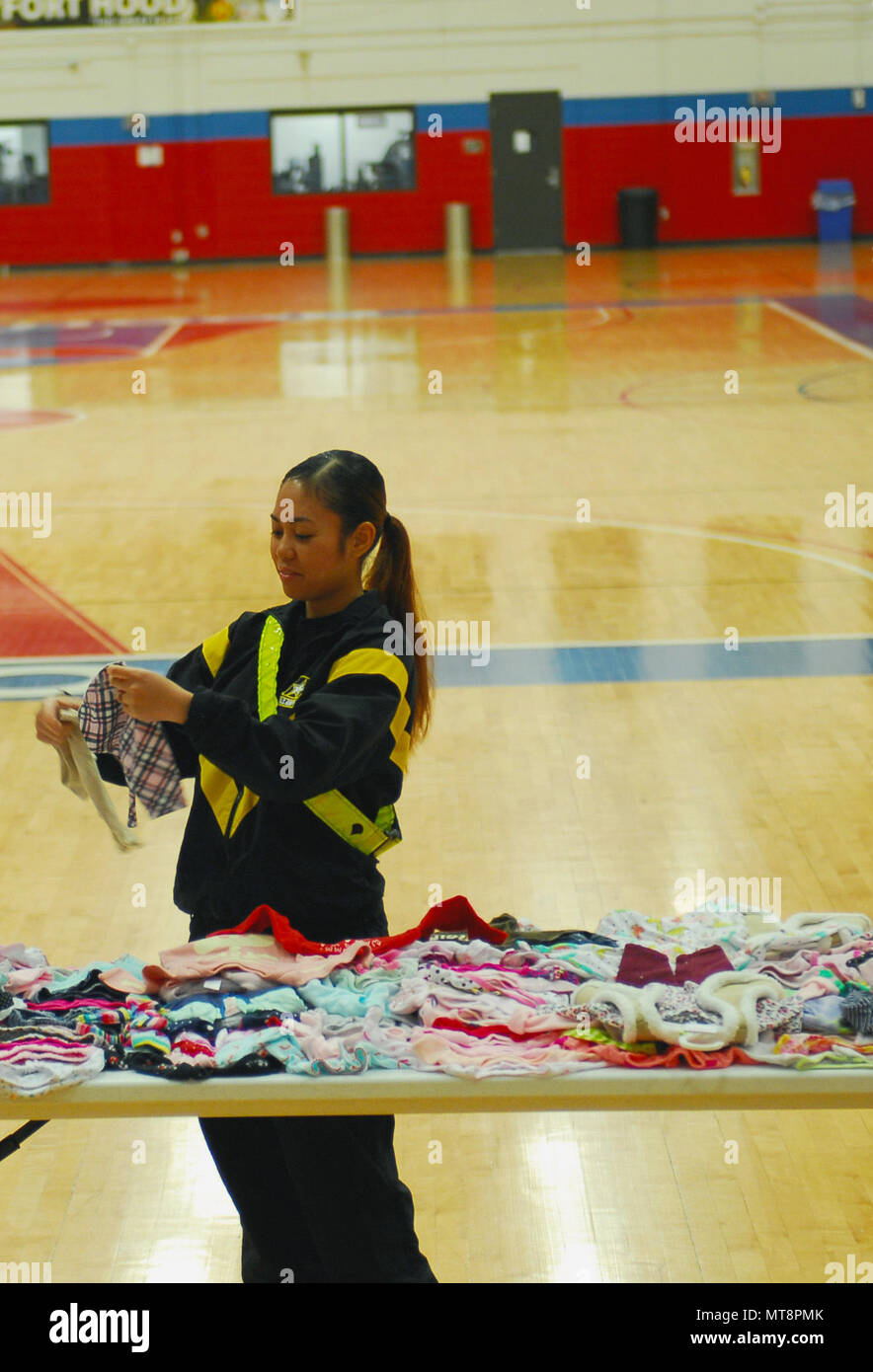 Spc. Diaresa Martinez, a food service specialist from 1st Battalion, 9th U.S. Cavalry Regiment, 2nd Armored Combat Team, 1st Cavalry Regiment, looks at baby clothes during Pregnancy Postpartum Physical Training Mother's Day baby clothing swap on Friday at Abrams gym. - Stock Image