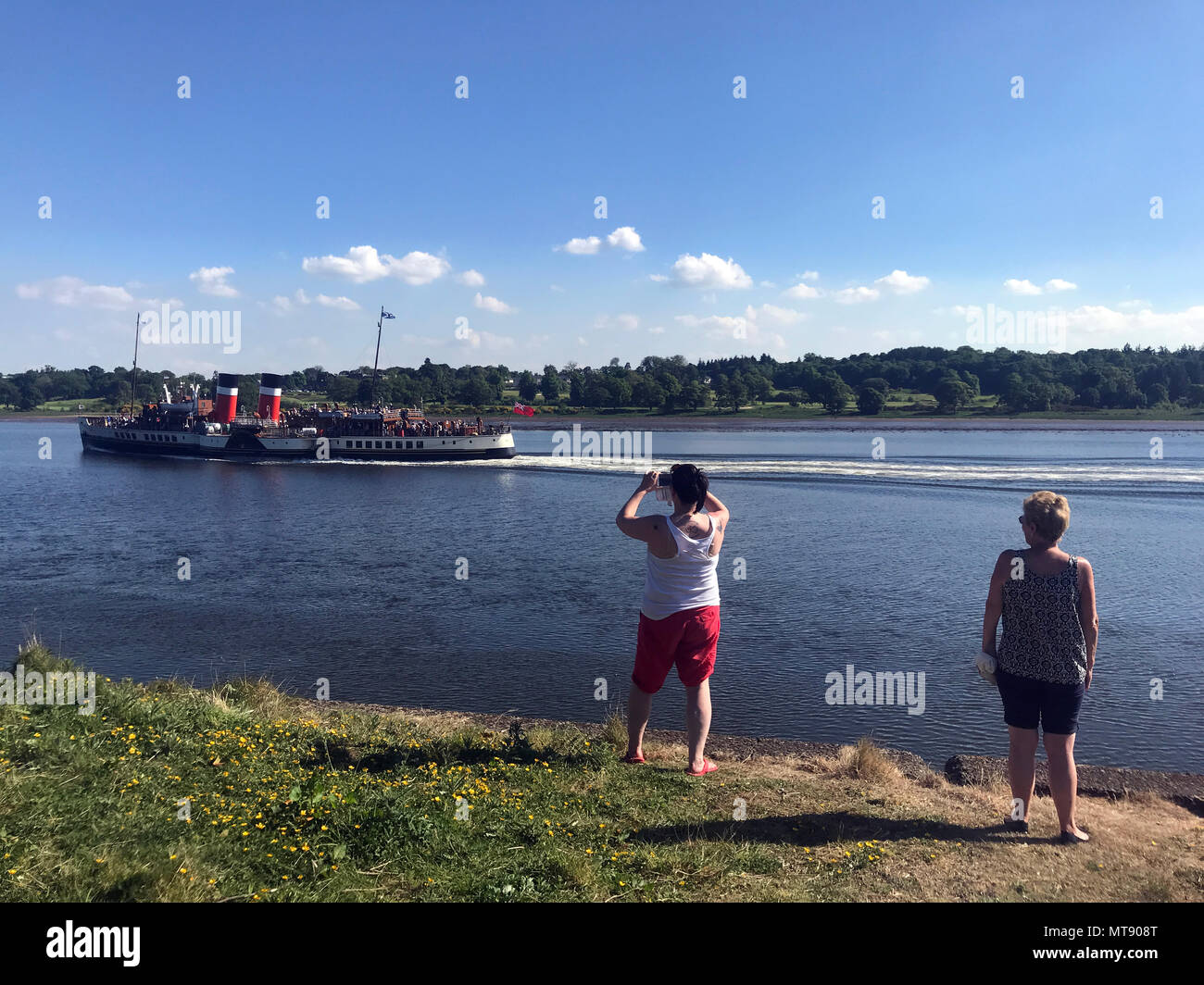 Glasgow, UK. 28th May, 2018. Members of the public take pictures of the PS Waverly as she travels up the River Clyde towards Glasgow, Scotland. PS Waverley is the last seagoing passenger-carrying paddle steamer in the world. Built in 1946, she sailed from Craigendoran on the Firth of Clyde to Arrochar on Loch Long until 1973.   28/5/18  Picture © Andy Buchanan 2018 Credit: Andy Buchanan/Alamy Live News Stock Photo