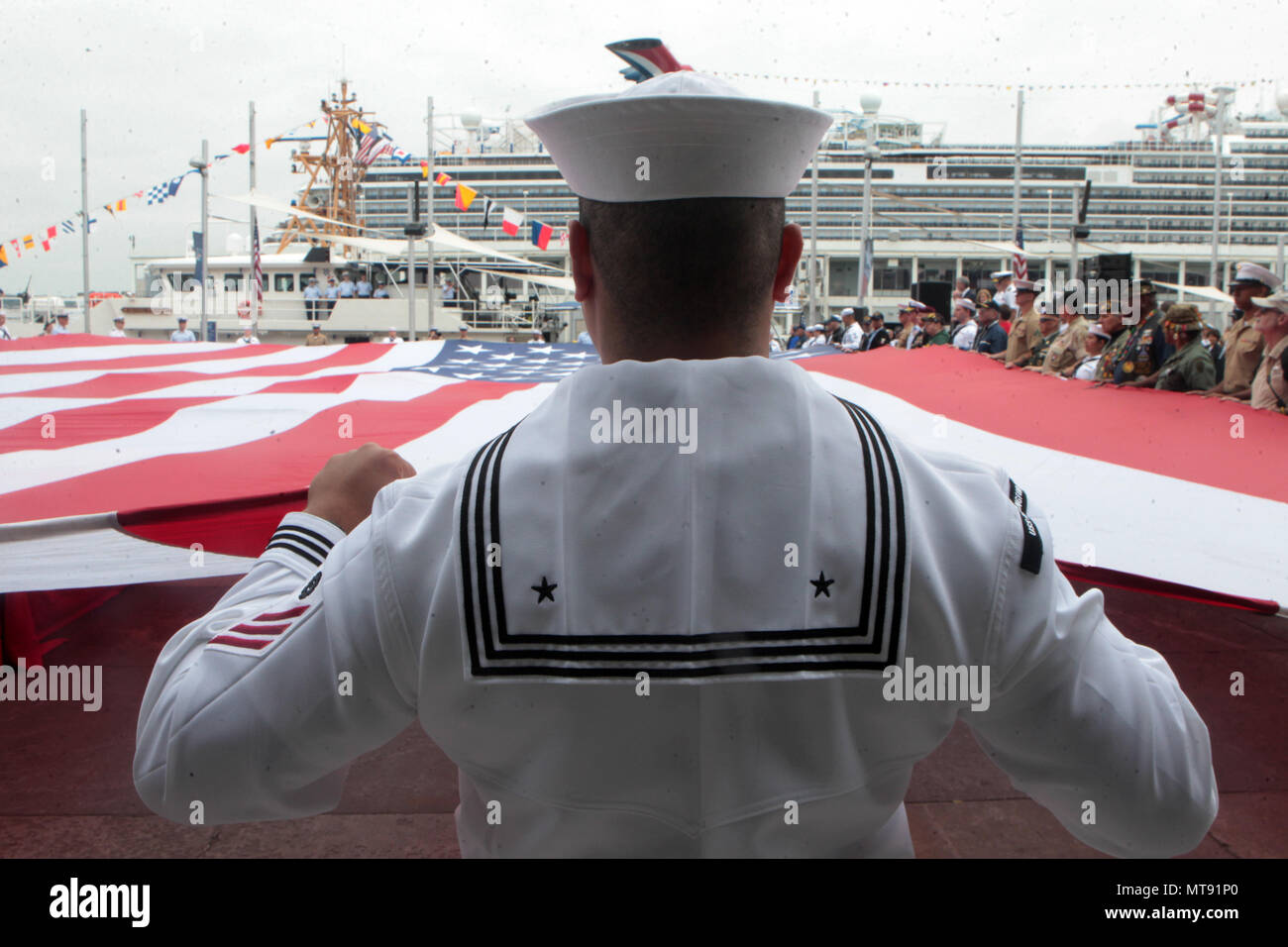 New York, NY, USA. 28th May, 2018. United States Soldiers comprised by representative of the Army, Navy, Airforce & Marines, along with participating members of the audience, unfurl a huge American flag as they attend the 2018 Memorial Day Ceremony held aboard the U.S.S Intrepid Sea, Air, Space Museum Complex on May 28, 2018 in New York City. Credit: Mpi43/Media Punch/Alamy Live News - Stock Image