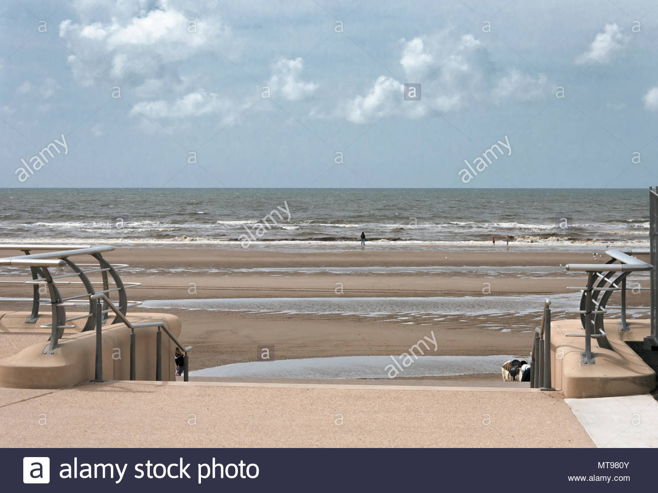 2008, An adult and a couple of children in the distance playing on an almost deserted sea front in Blackpool England, while restoration work was ongoi - Stock Image