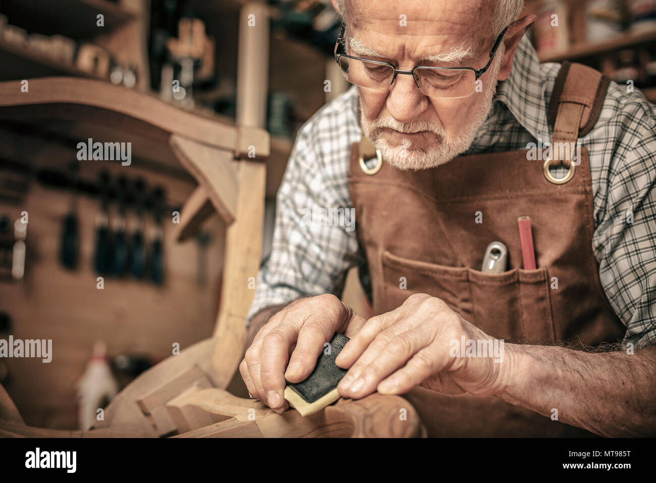 carpenter engaged in polishing an unfinished chair - Stock Image