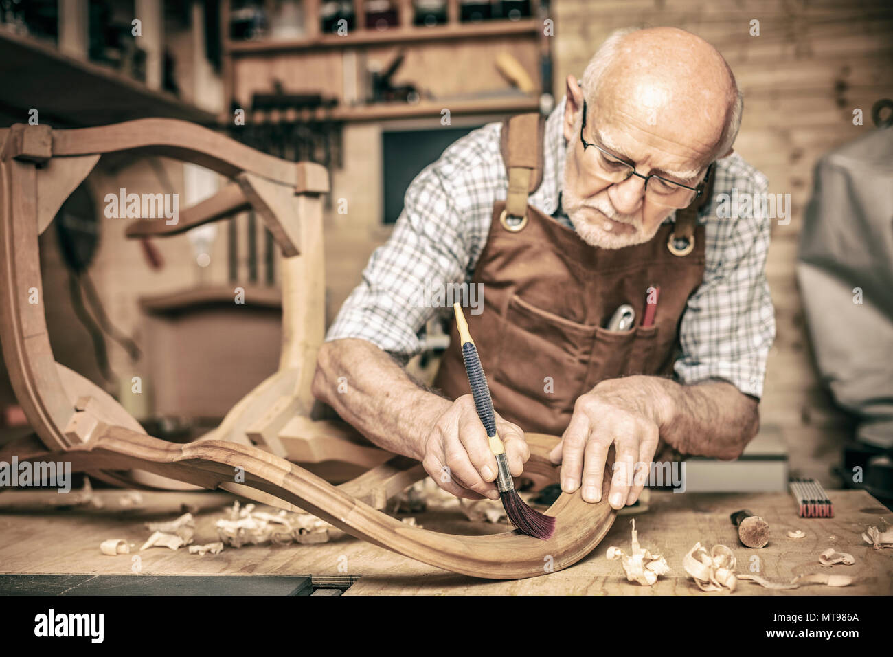 elderly carpenter uses a brush on an unfinished chair - Stock Image