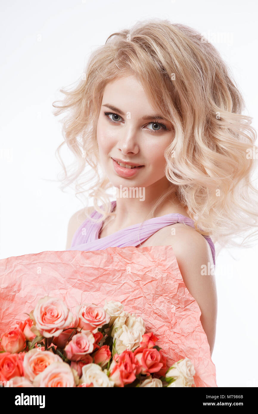 Portrait of beautiful curly blondy woman with perfect make-up. Holding bouquet - Stock Image