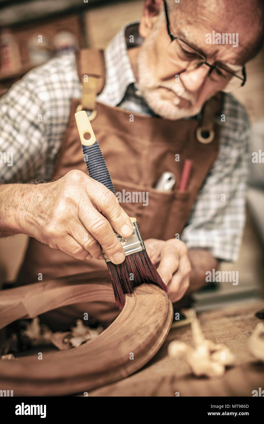 elderly carpenter uses a brush on an unfinished chair Stock Photo