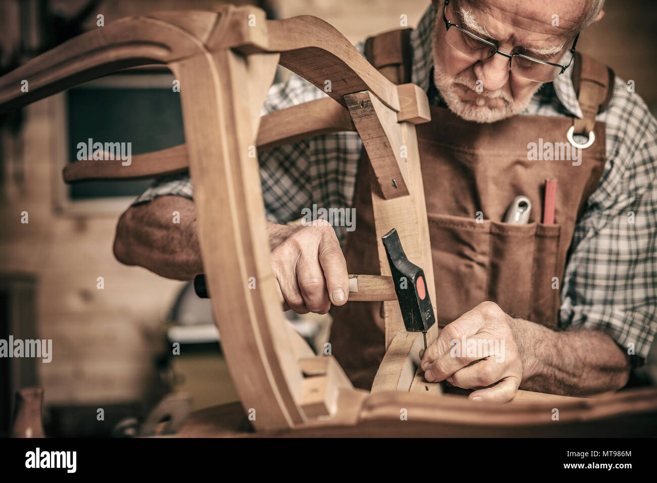 elderly carpenter builds a classic style chair - Stock Image