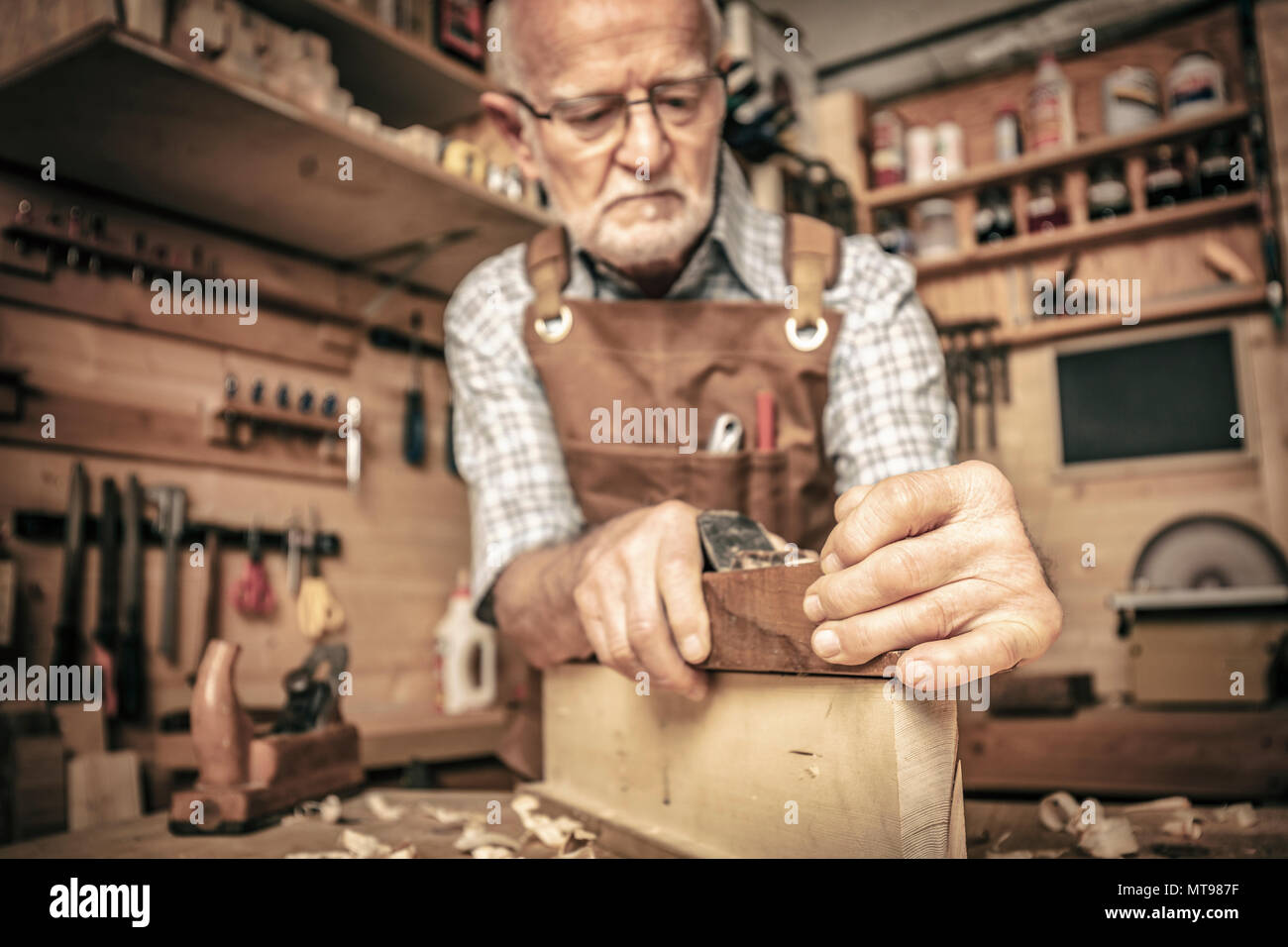 old carpenter uses a planer - Stock Image