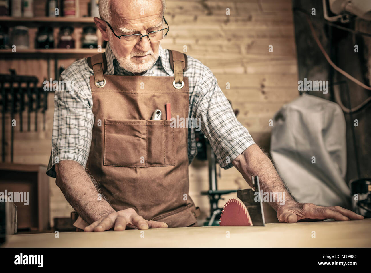 professional carpenter works with a saw bench in his workshop - Stock Image