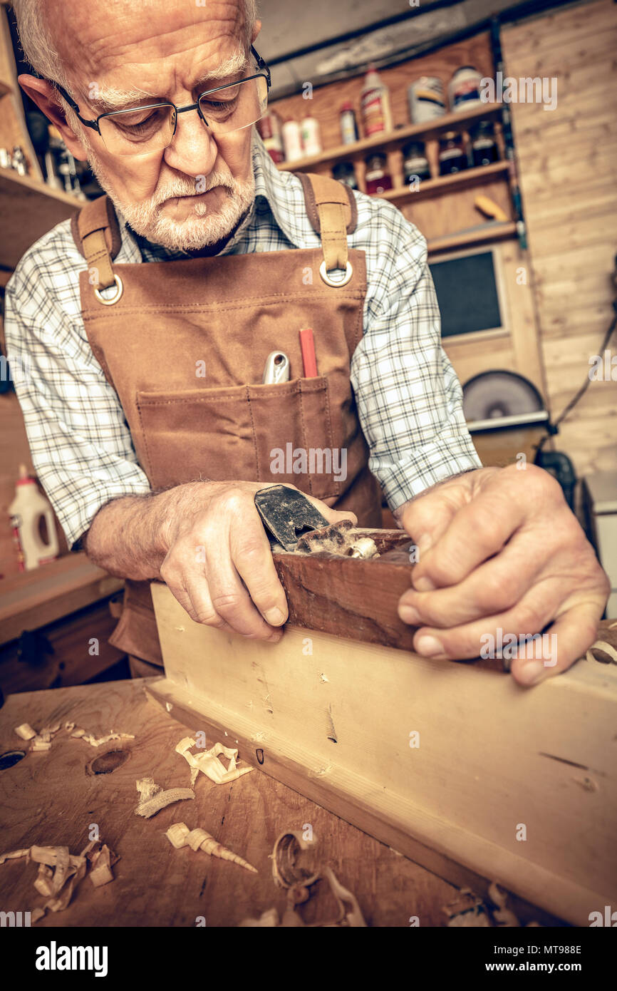 professional carpenter works with the planer on a beam - Stock Image