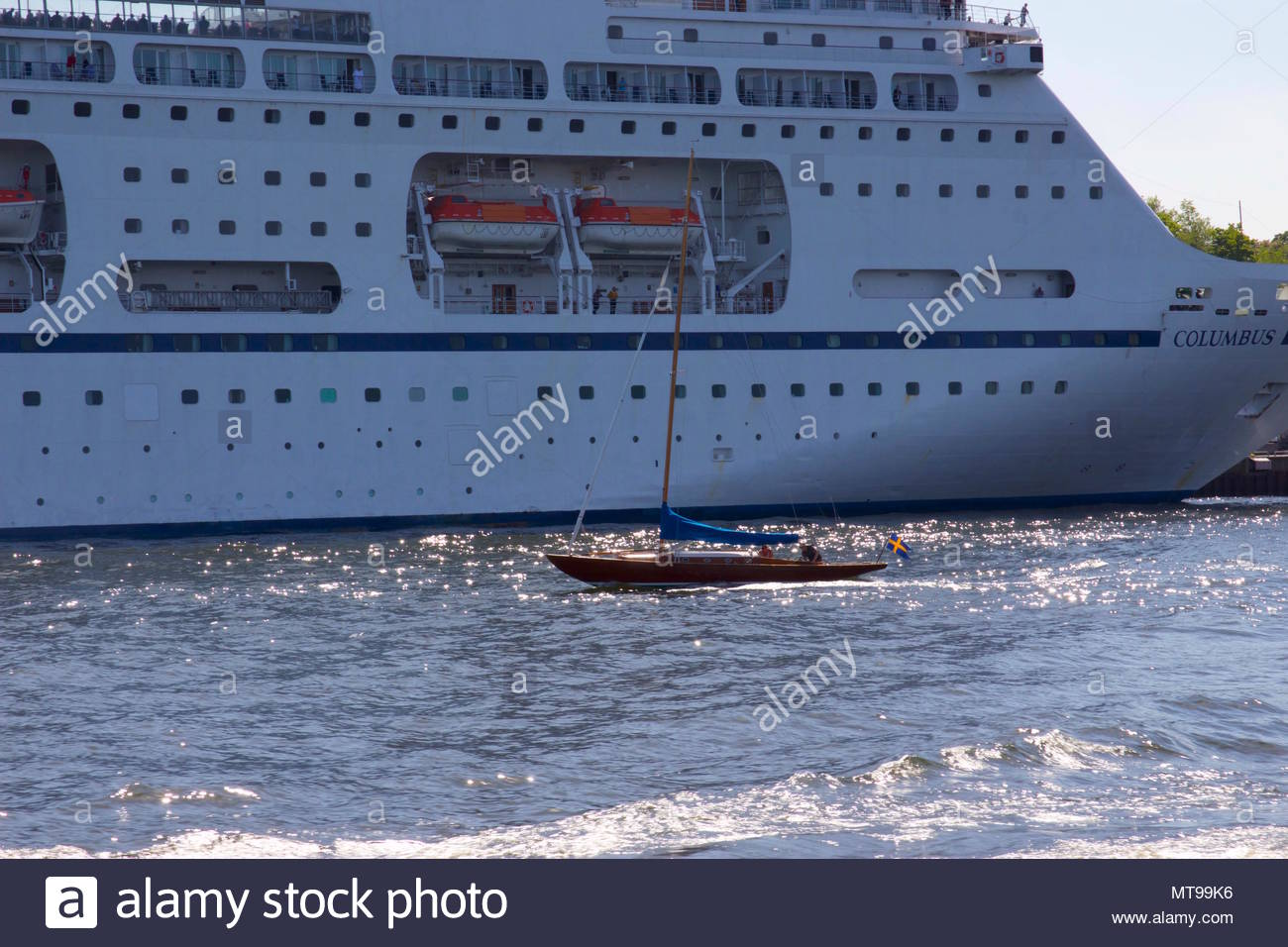 The Viking Line Cruise Ship next to a small wooden sail boat with a Swedish flag on the Baltic Sea in Stockholm, Sweden - Stock Image