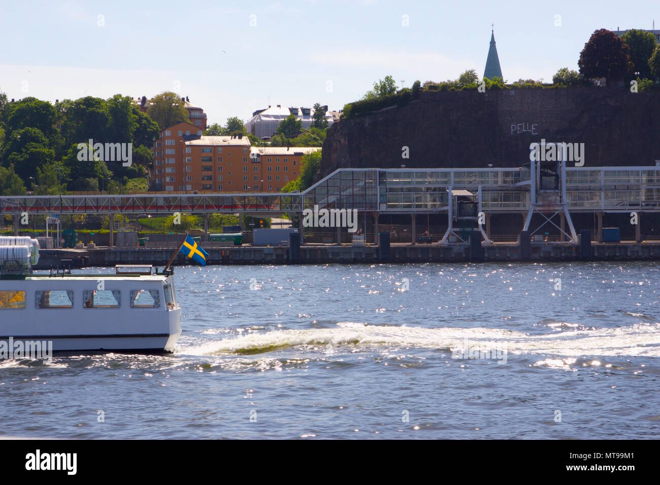 White boat with a Swedish flag on the Baltic Sea in the Stockholm Archipelago - Stock Image