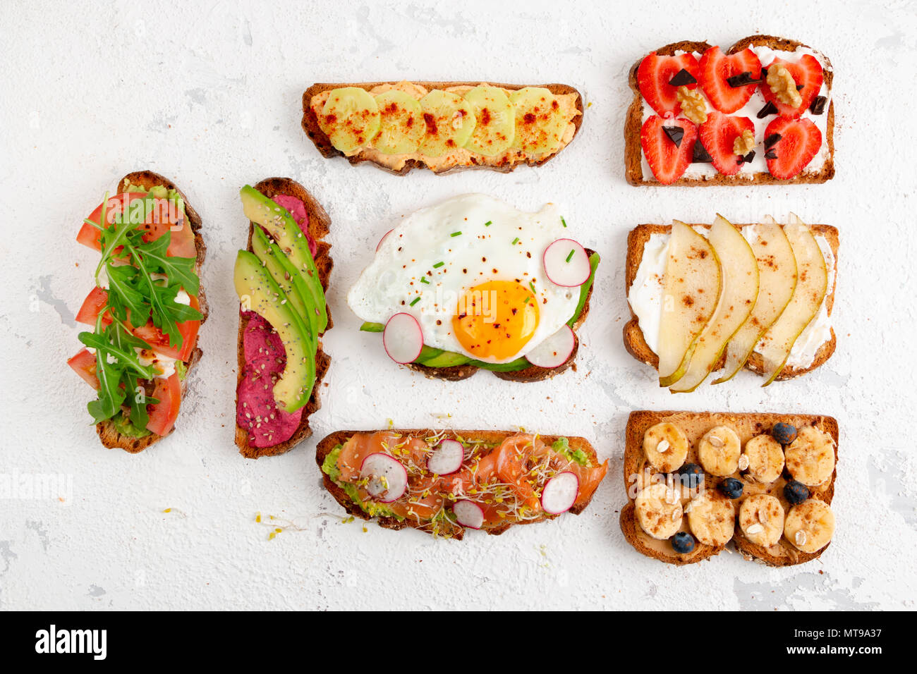 Assortment of healthy breakfast toasts on a white rustic background. Top view, flat lay - Stock Image