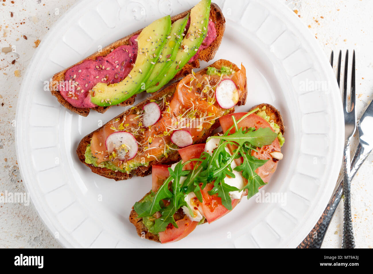 Assortment of healthy breakfast toasts on a dish on a white rustic background. Top view - Stock Image