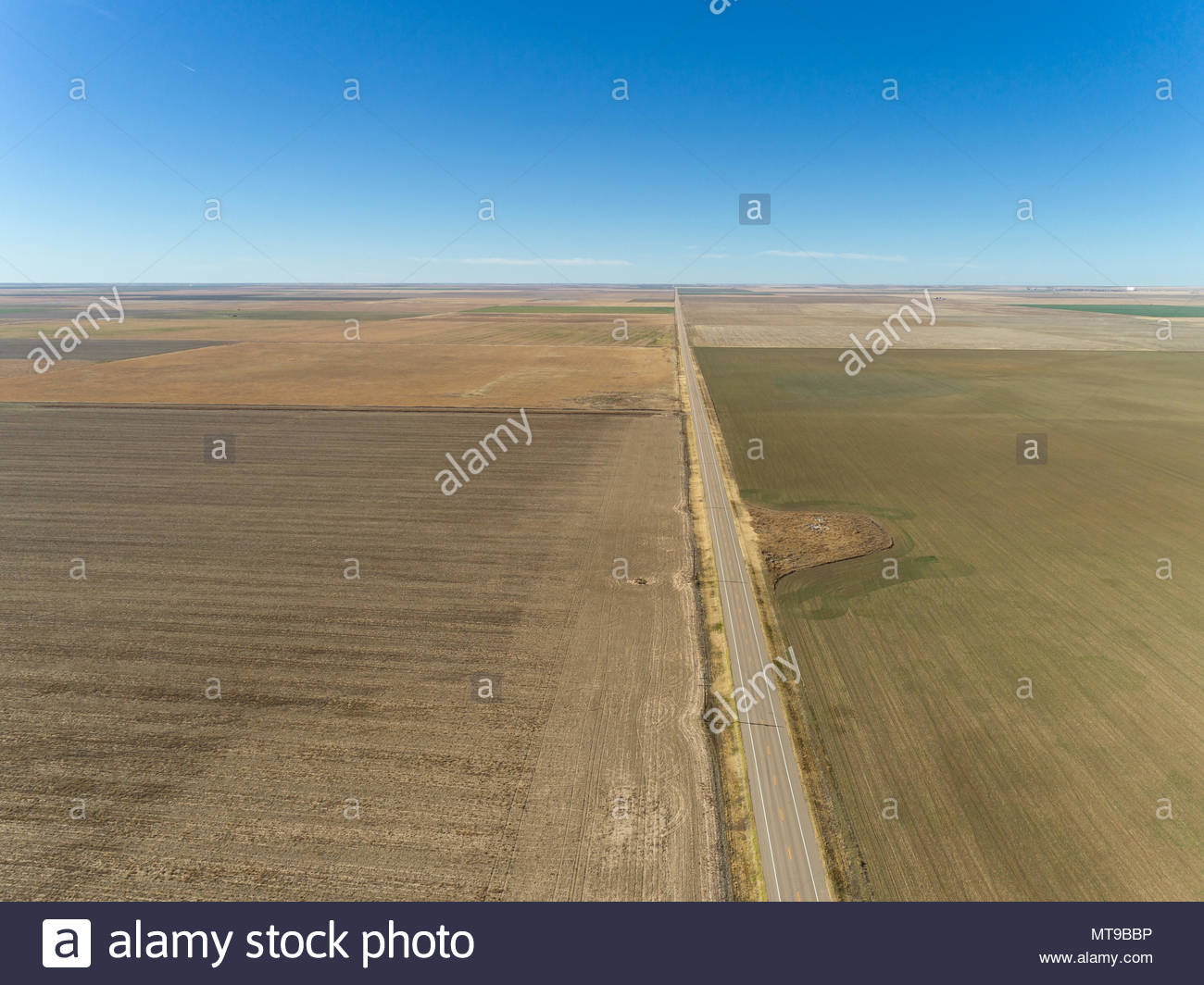 A flat landscape of plowed empty fields and an empty road leads to the horizon in northwestern Oklahoma. Stock Photo