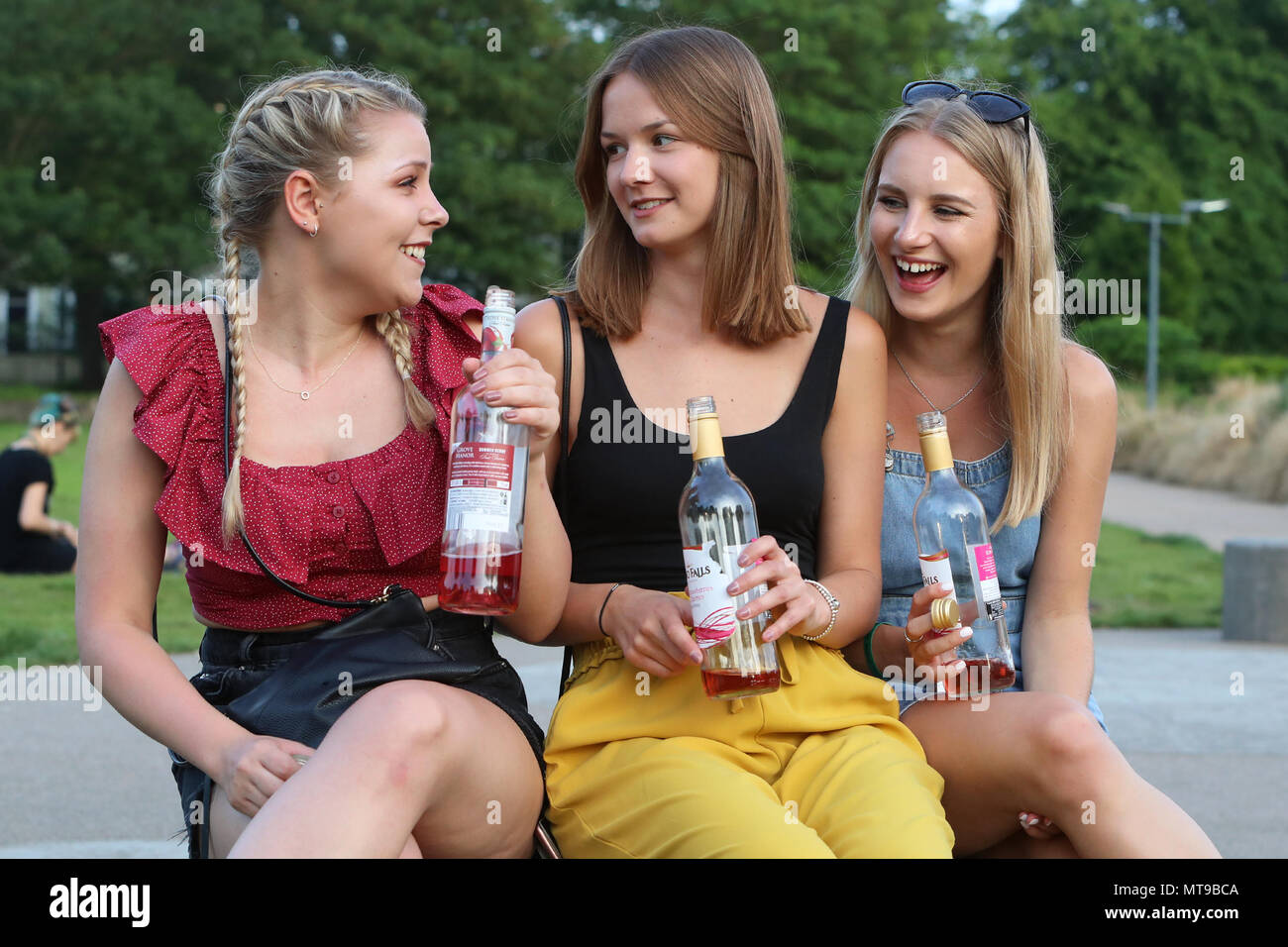 Three young women drinking wine in a Brighton park - Stock Image