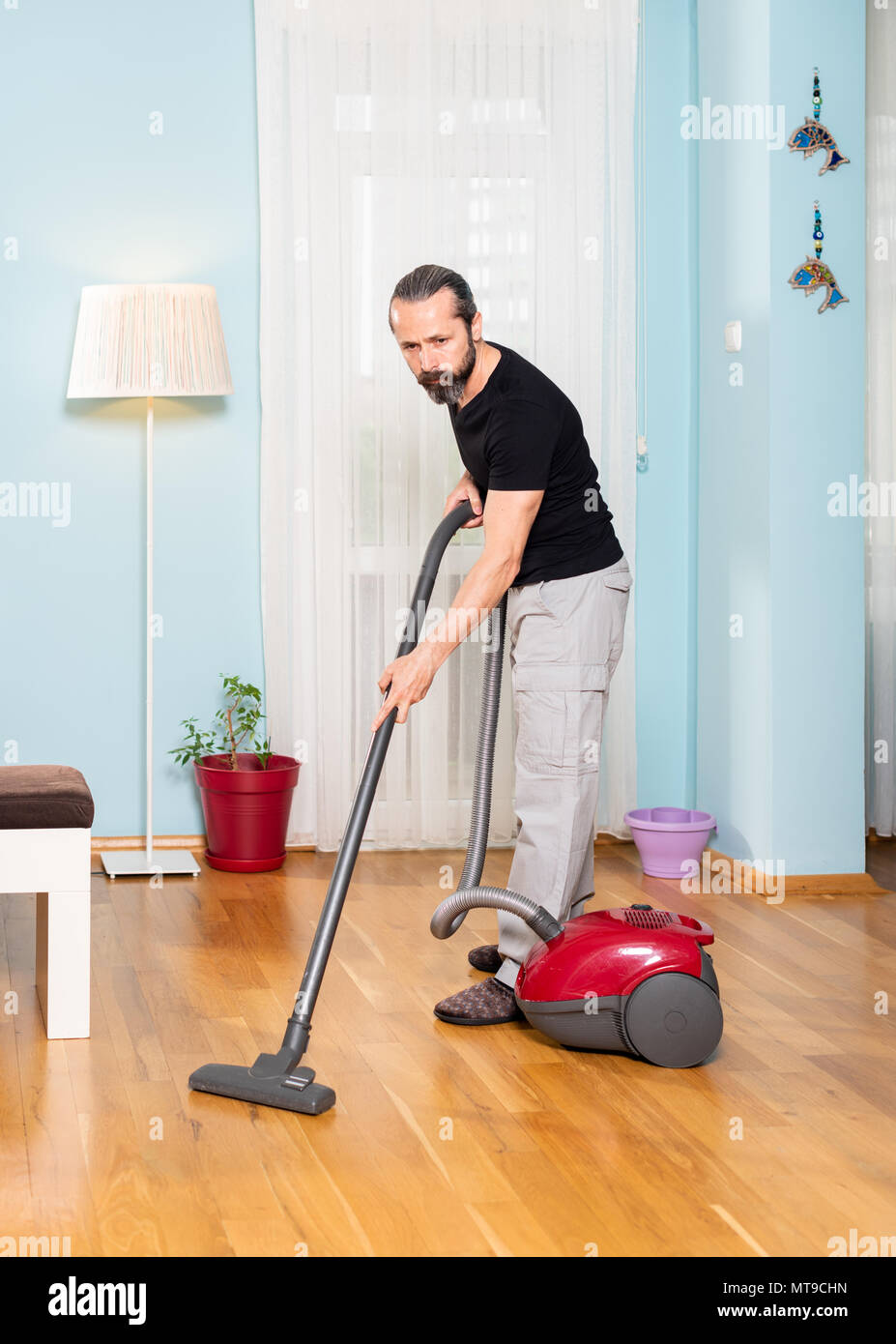 House sweeping man, sweeping wood work with broom machine - Stock Image