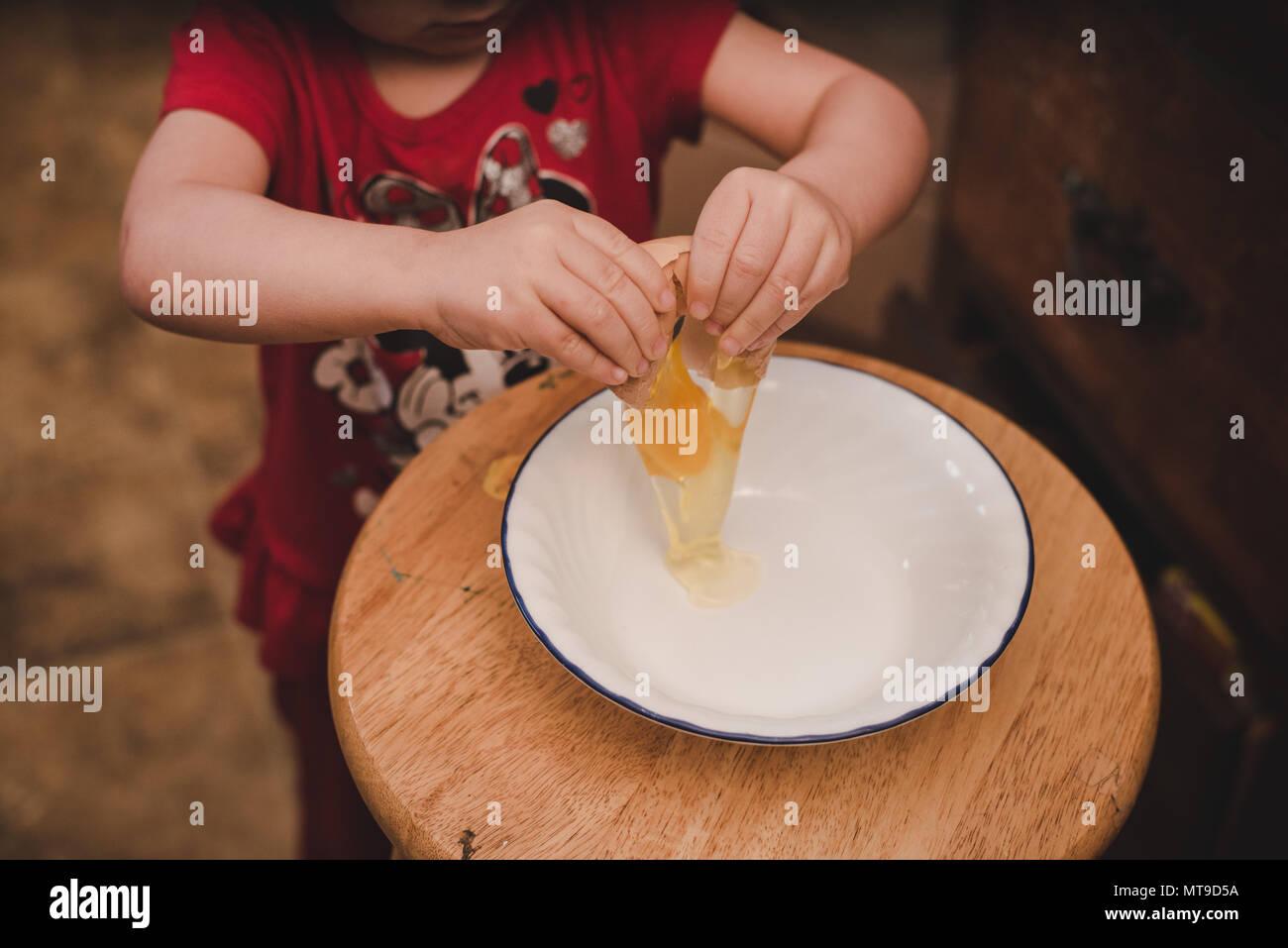 A toddler cracking a farm fresh egg into a bowl. - Stock Image